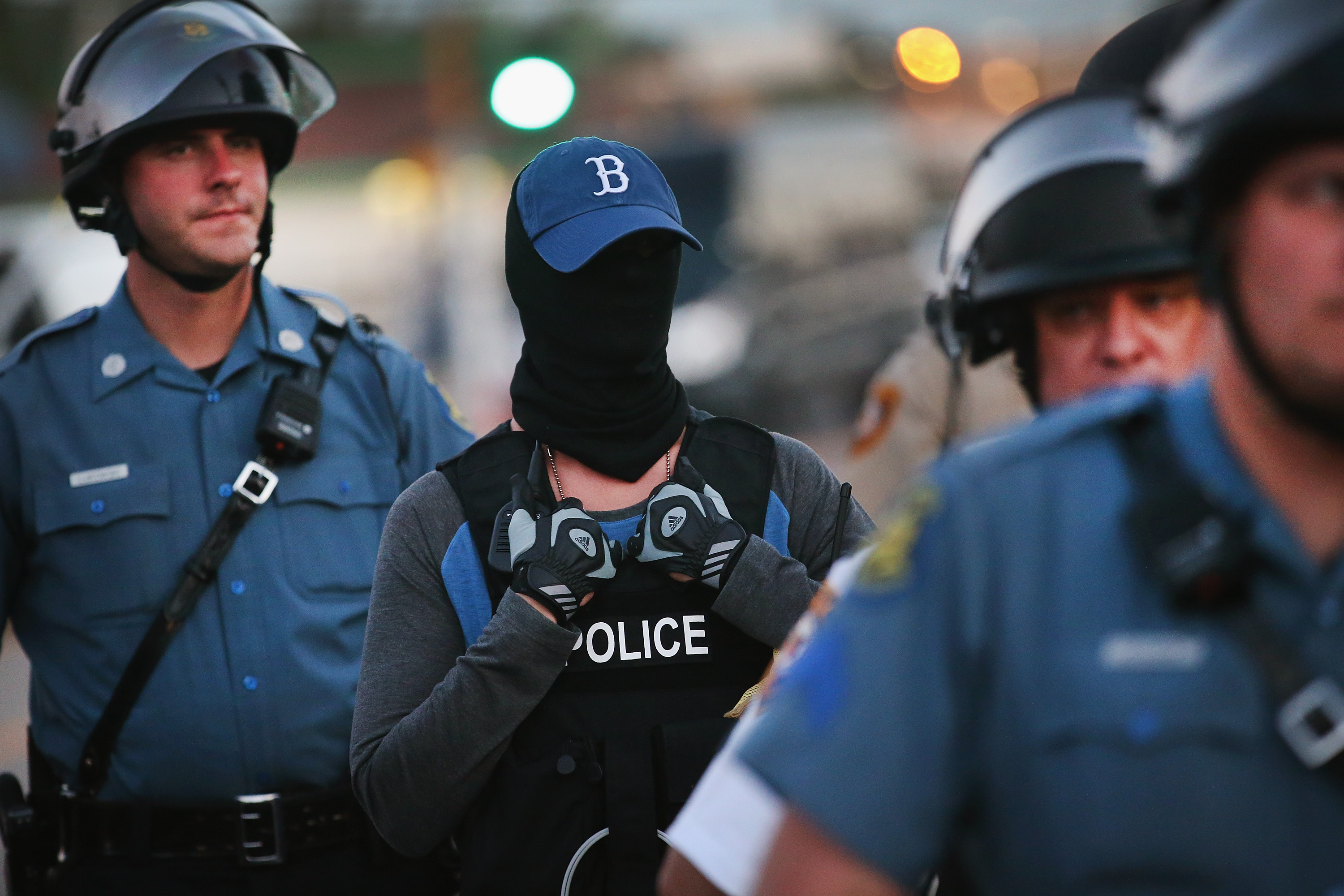 A police officer standing watch as demonstrators protest the shooting death of teenager Michael Brown conceals his/her identity on August 13, 2014 in Ferguson, Missouri.