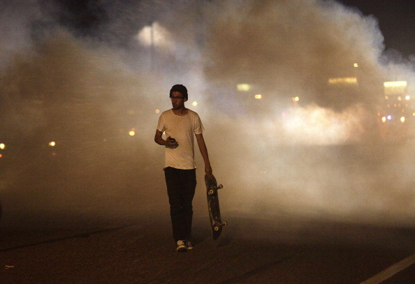A man with a skateboard protesting the shooting of Michael Brown by a police officer walks away from tear gas released by police August 17, 2014 in Ferguson, Missouri.