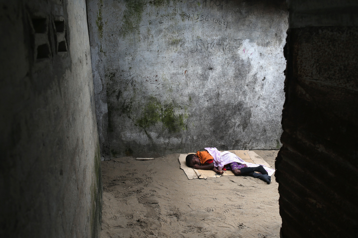 Aug. 19, 2014. A very sick Saah Exco, 10, lies in a back alley of the West Point slum in Monrovia, Liberia. The boy was one of the patients that was pulled out of a holding center for suspected Ebola patients when the facility was overrun by a mob on Saturday.