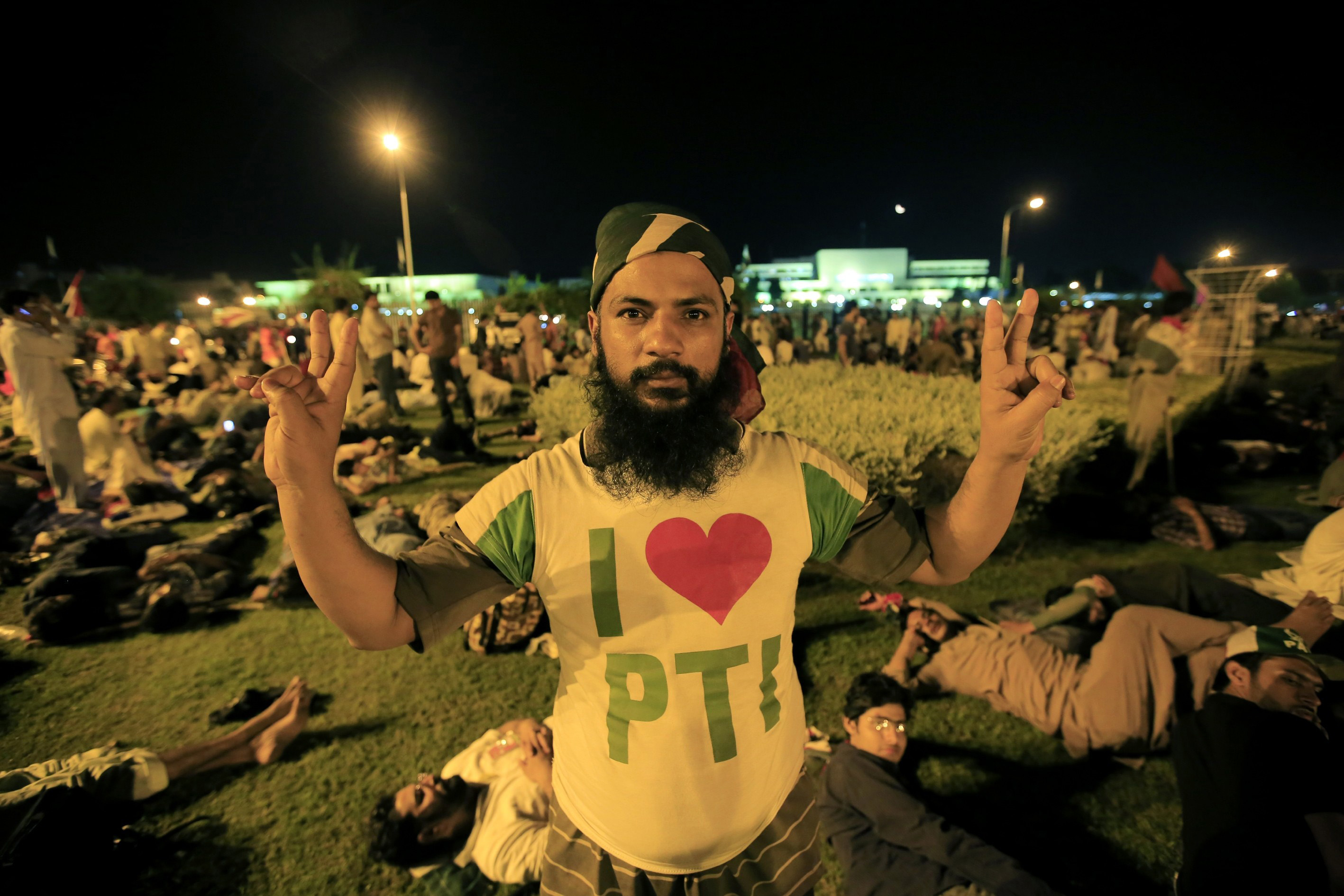 Pakistani political party Pakistan Awami Tehreek (PAT) members celebrate  entering the Red Zone in Islamabad, Pakistan, on August 20, 2014. Thousands of protesters ran over the barricades and entered Pakistani capital Islamabad's sensitive Red Zone area, which houses state buildings, on Tuesday night as the heavy force deployed there offered no resistance. Chanting anti-government slogans, protesters wanted to topple the government.