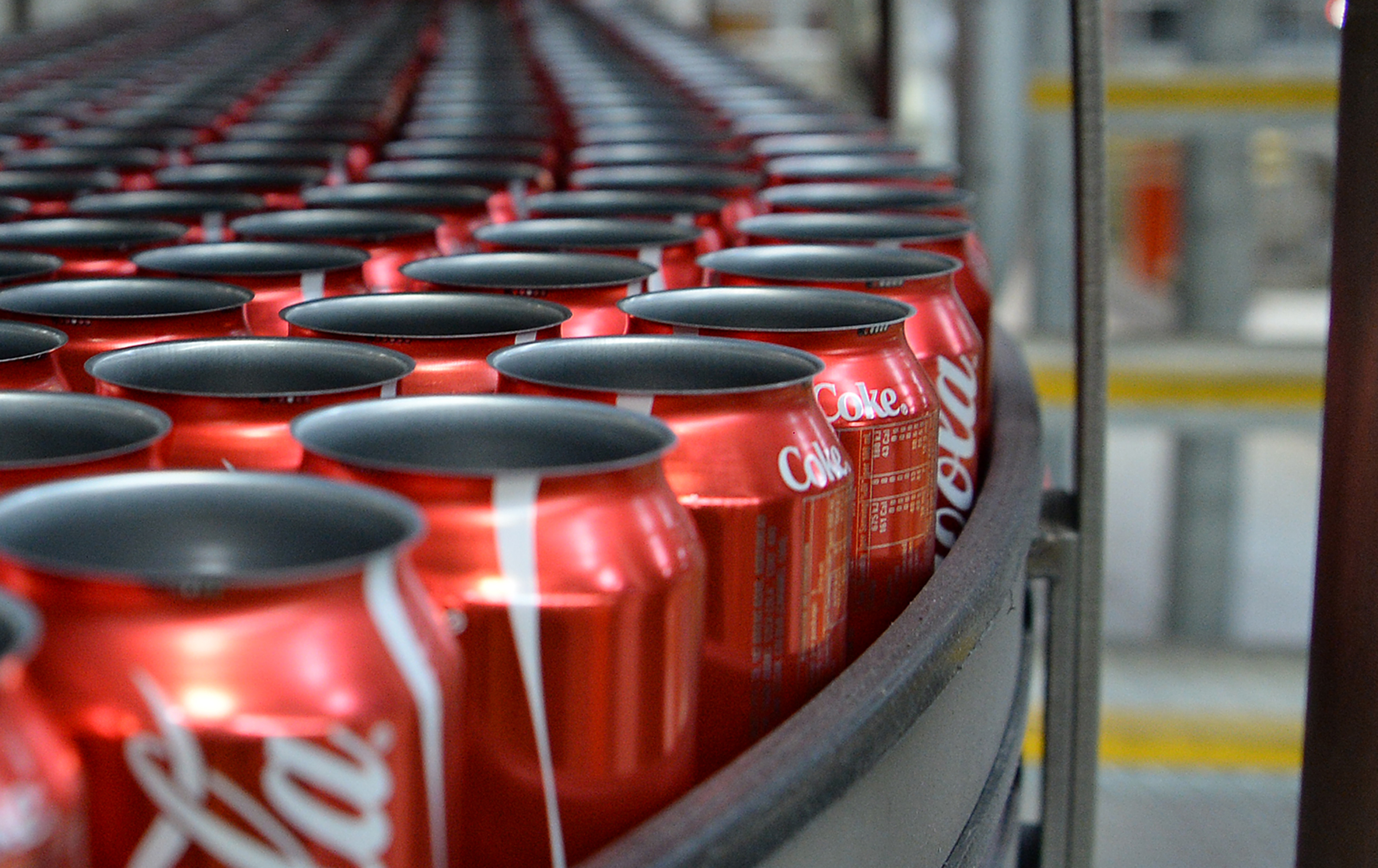 Empty Coca-Cola Classic cans move along a conveyor to be filled.