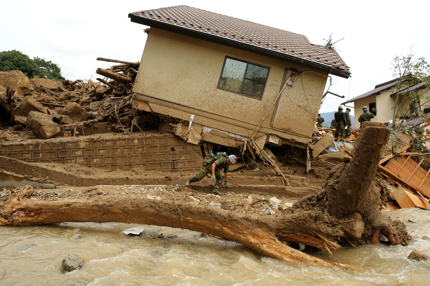 Aug. 20, 2014. Members of Ground Self-Defense continue the search for missing people among the debris of houses destroyed by a landslide caused by torrential rain at the site of a landslide in a residential area on in Hiroshima, Japan.