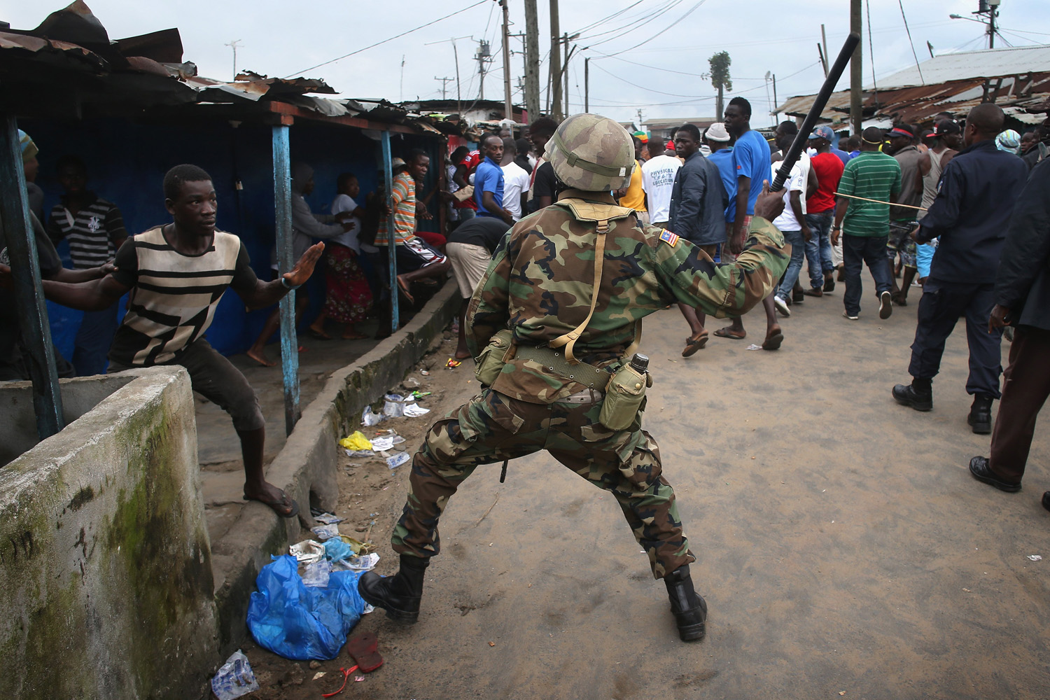 Aug. 20, 2014. A Liberian Army soldier, part of the Ebola Task Force, beats a local resident while enforcing a quarantine on the West Point slum in Monrovia, Liberia. The government ordered the quarantine of West Point, a congested seaside slum of 75,000, on Wednesday, in an effort to stop the spread of the virus in the capital city.