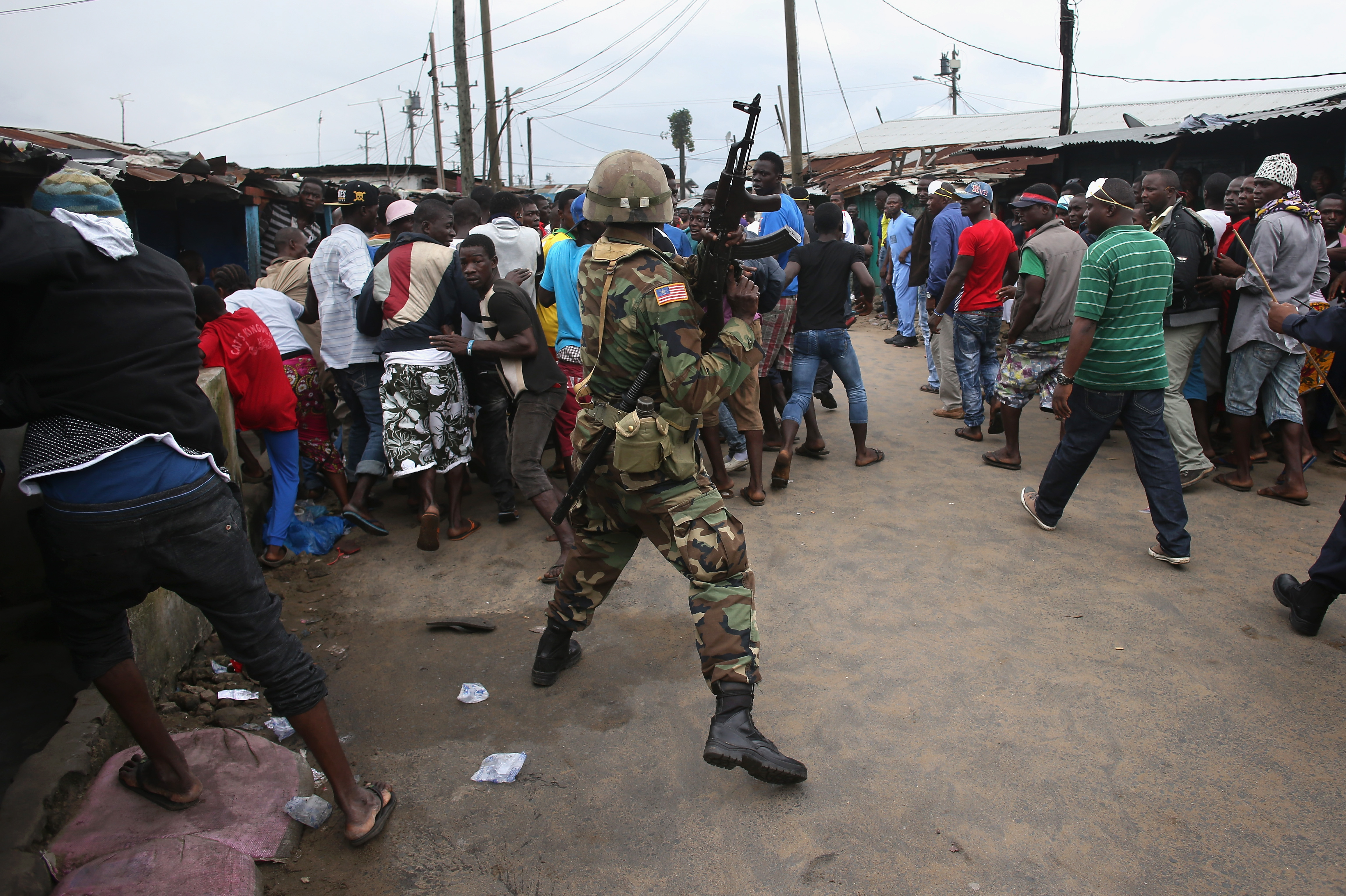 A Liberian Army soldier, part of the Ebola Task Force, pushes back local residents while enforcing a quarantine on the West Point slum on August 20, 2014 in Monrovia, Liberia.