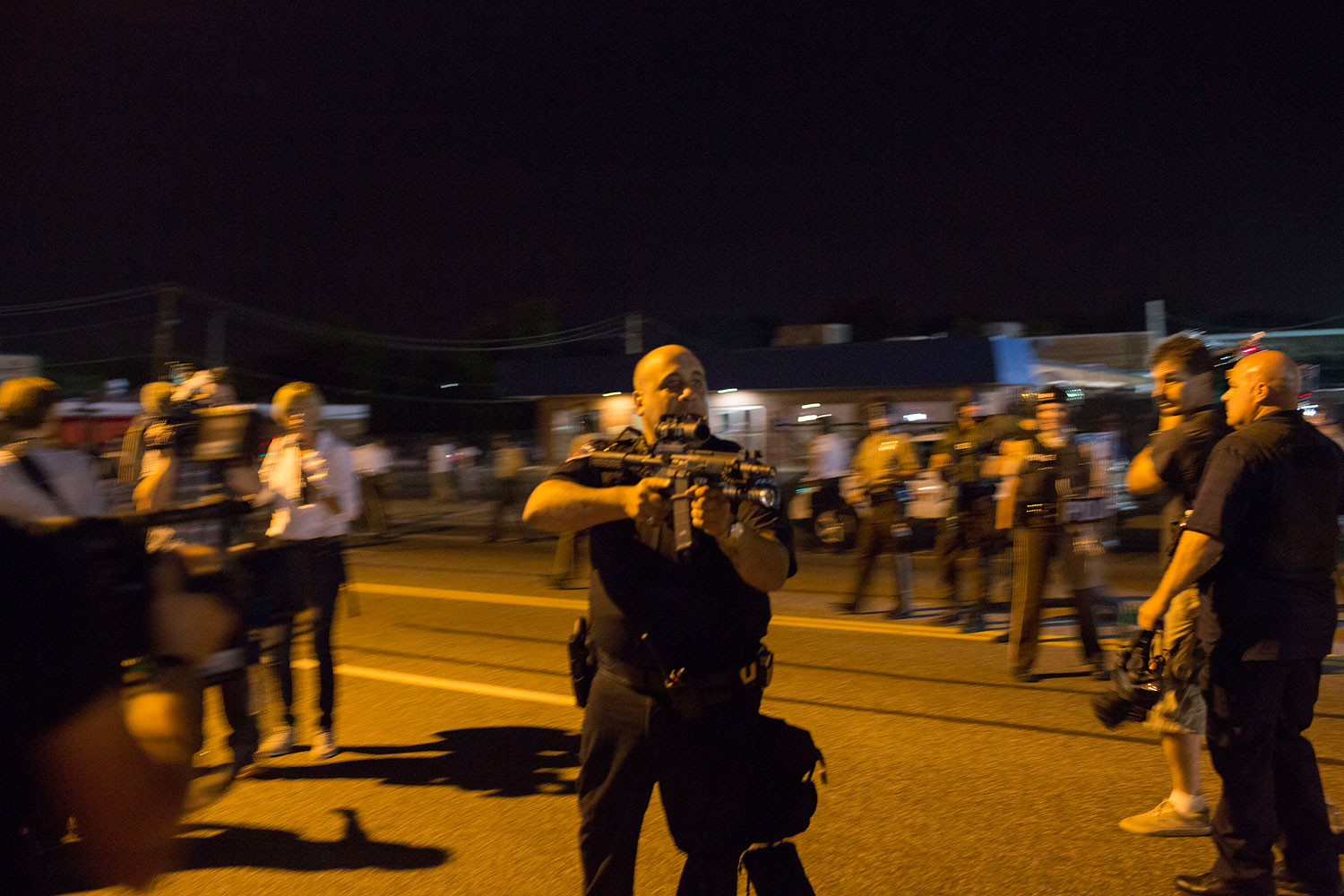 St. Ann, Missouri police officer Lt. Ray Albers points an assault rifle at a protester, Aug. 19, 2014 in Ferguson, Missouri.