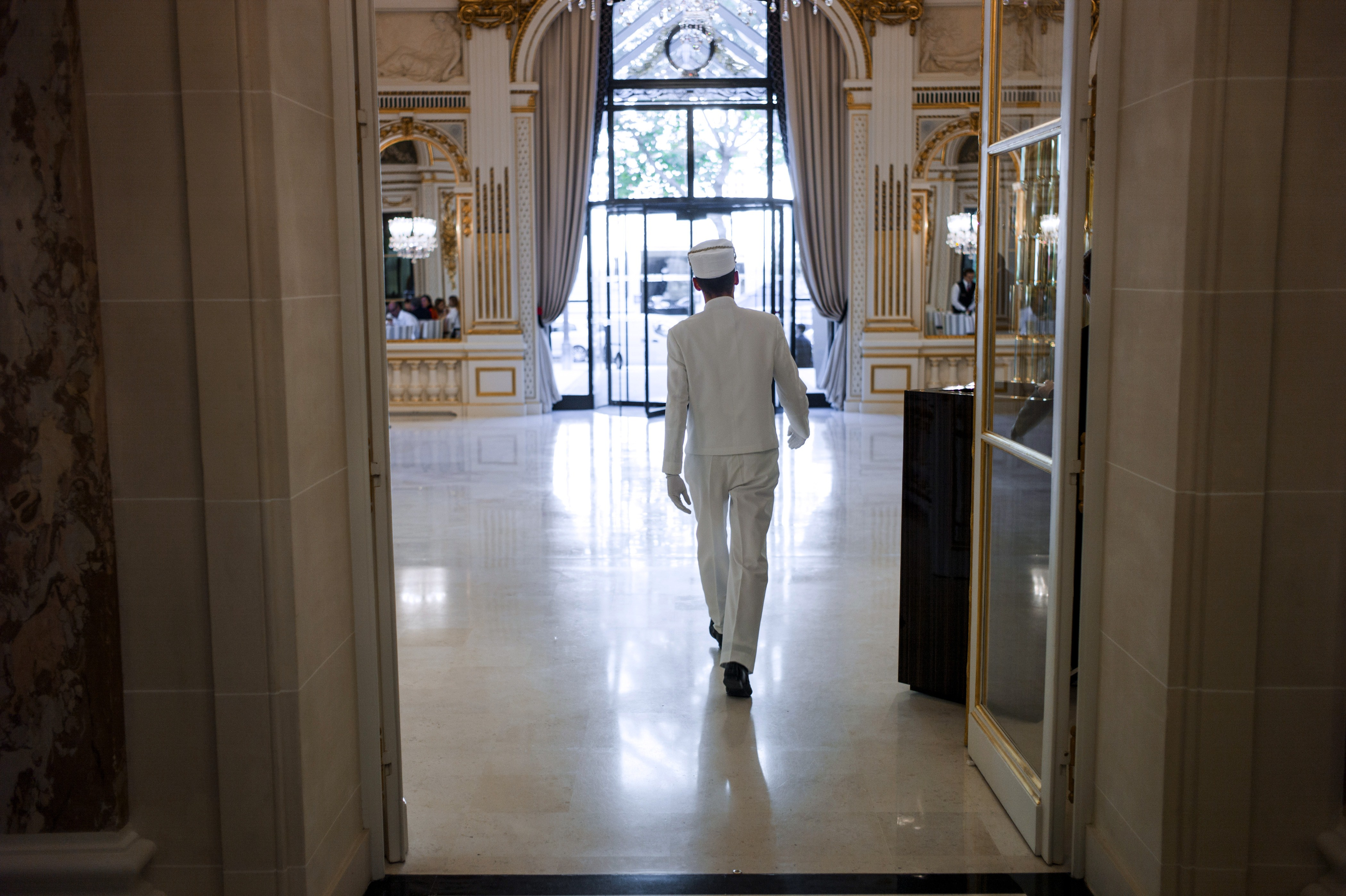 A bellhop walks at the entrance of the  The Peninsula Paris  hotel on August 21, 2014 in Paris.