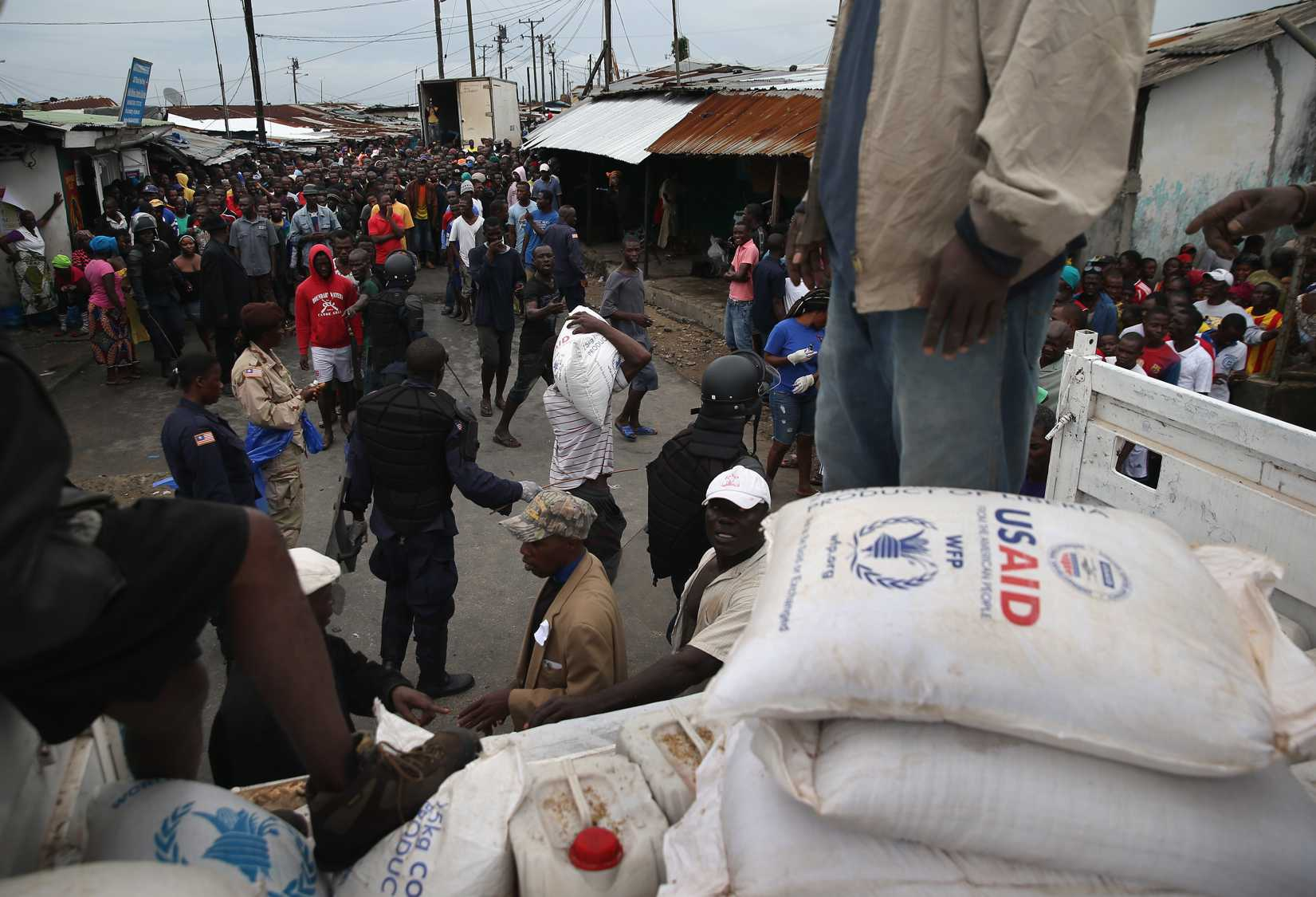 Residents of the West Point slum receive food aid during the second day of the government's Ebola quarantine on their neighborhood on August 21, 2014 in Monrovia, Liberia.