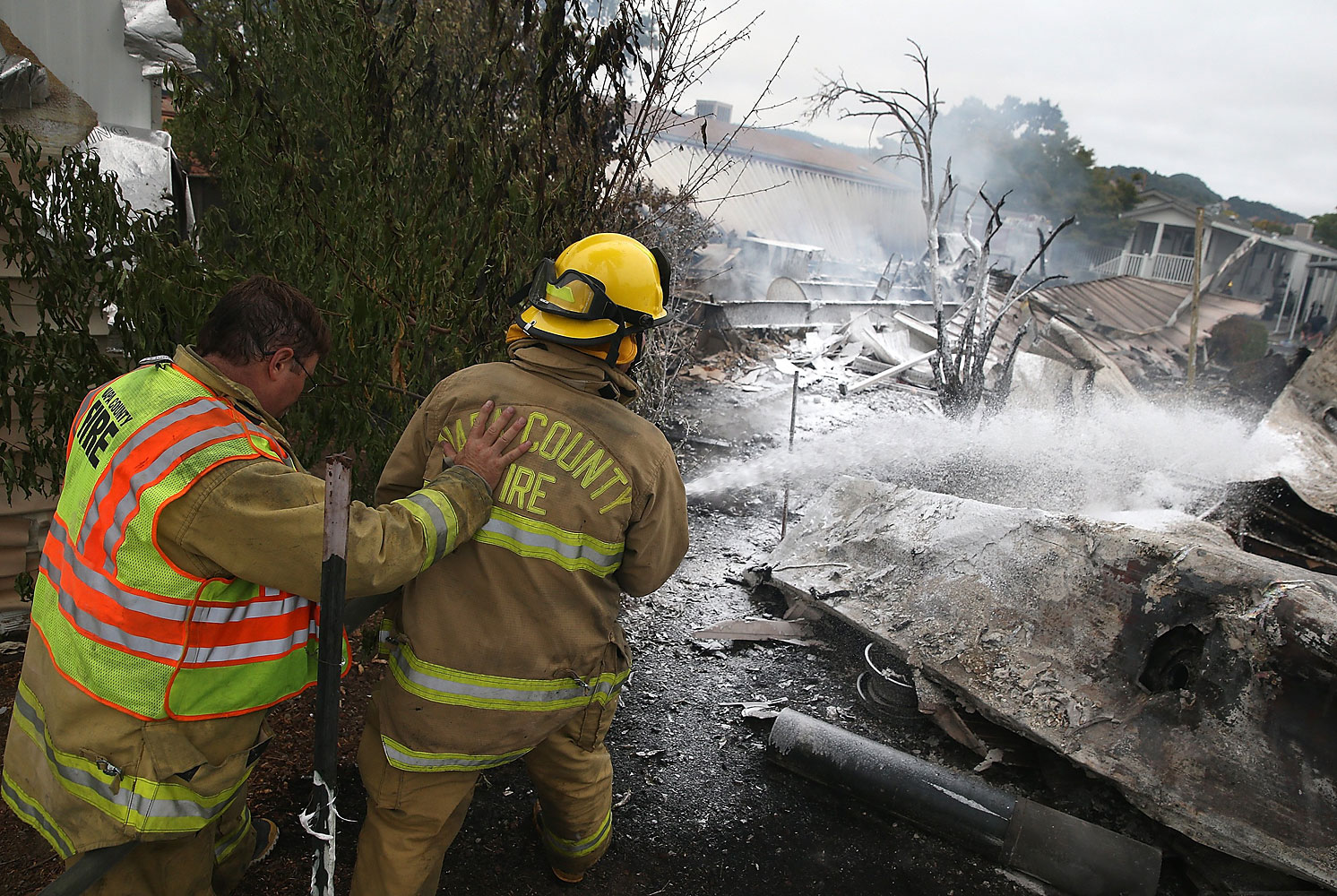 Napa County firefighters spray foam on hot spots from a fire at a mobile home park following the earthquake, in Napa, Calif.
