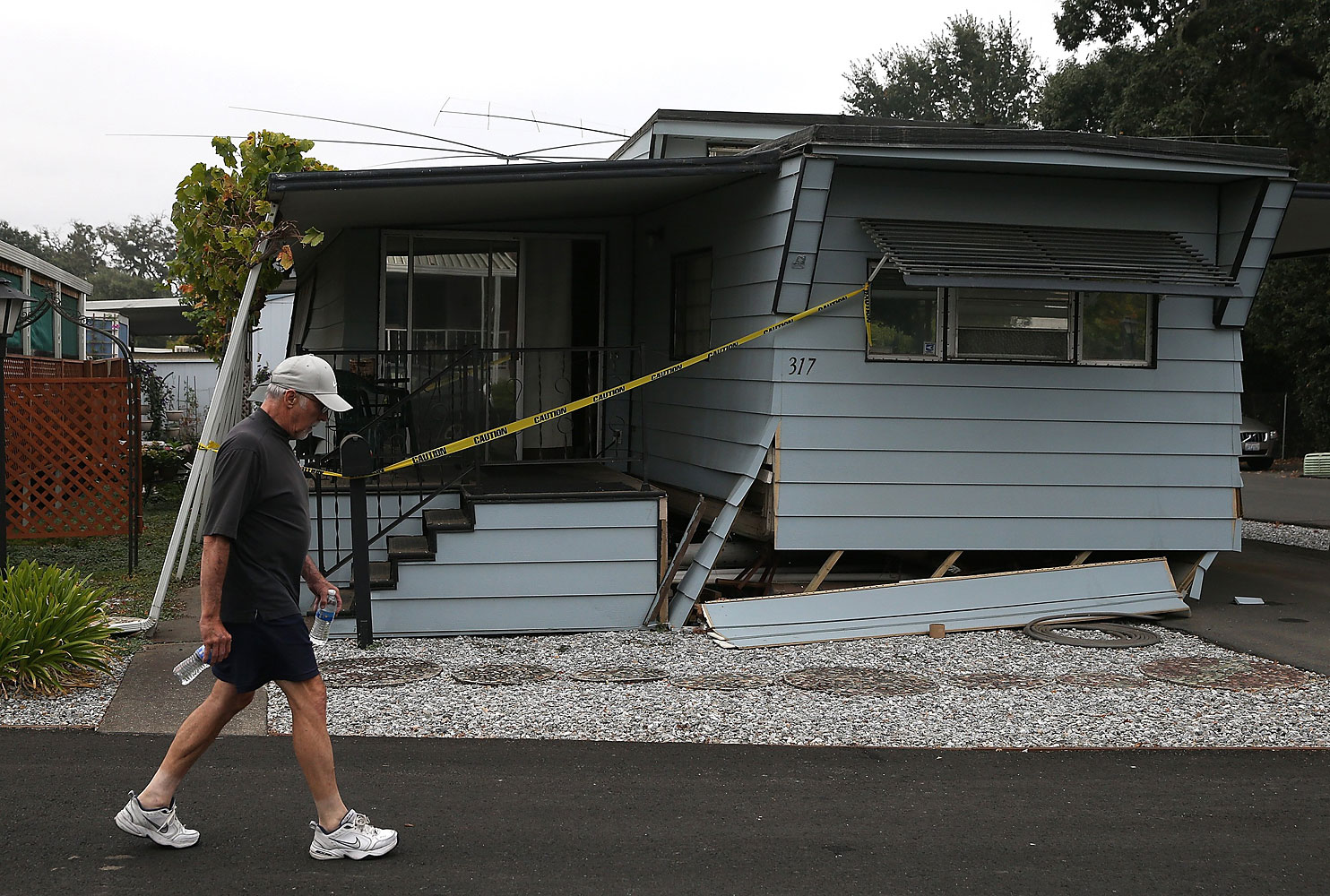 A pedestrian walks by a mobile home that shifted off of its foundation in Napa, Calif.