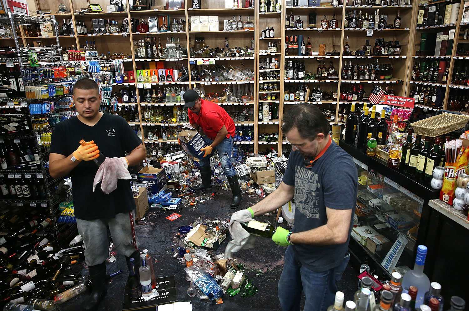 Workers clean up piles of bottles that were thrown from the shelves at Van's Liquors in Napa, Calif.