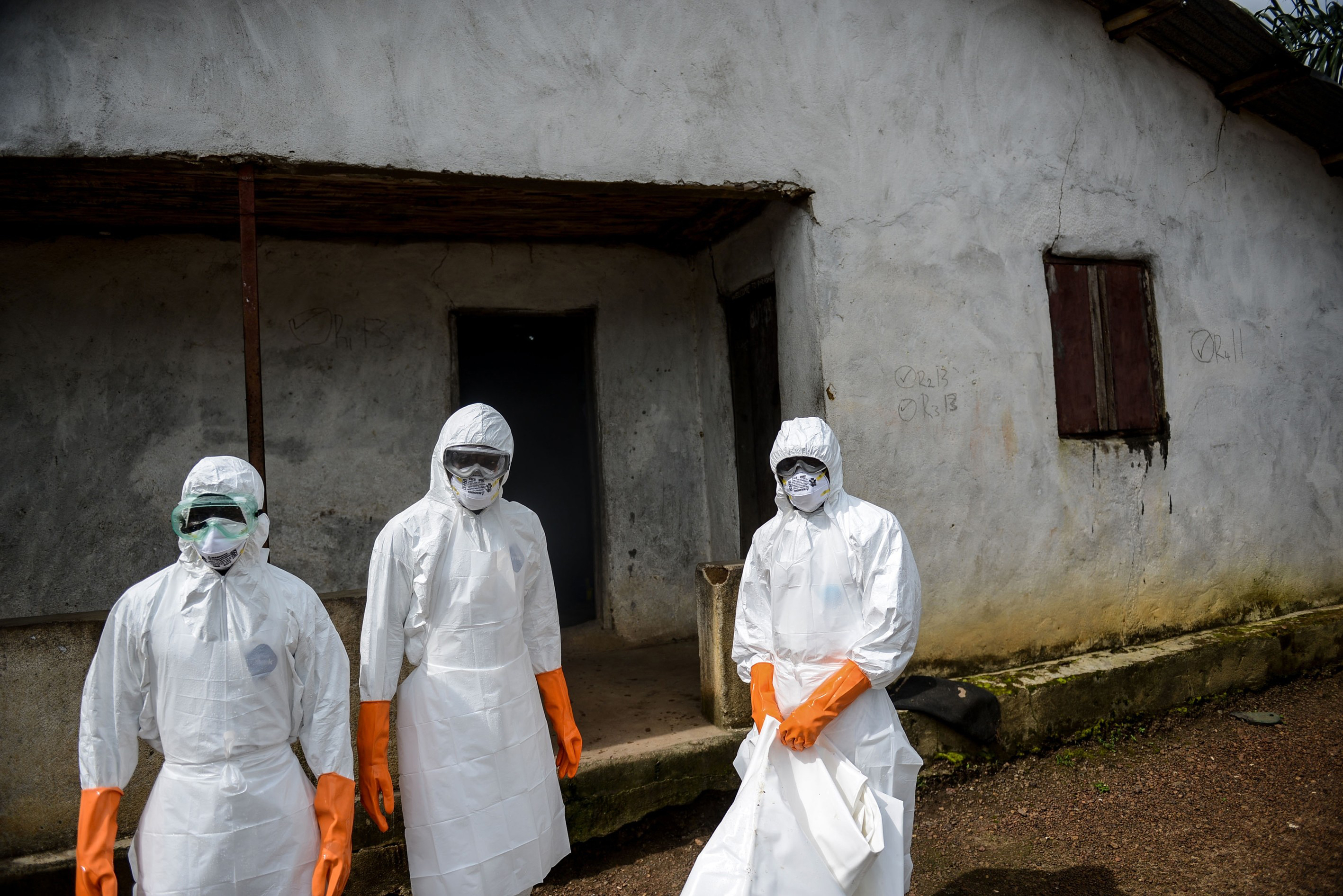 A group of young volunteers wear special uniforms sterilize round the house after Baindu Koruma (28) died due to the Ebola virus, in Lango village, Kenema, Sierra Leone on August 25, 2014.