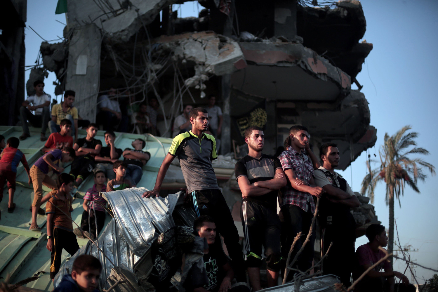 Aug. 27, 2014. Palestinian men listen the press statement of the members of the Ezzeddin al-Qassam Brigades, the armed wing of Palestinian resistance faction Hamas, in the Shujaya neighborhood in eastern Gaza City.