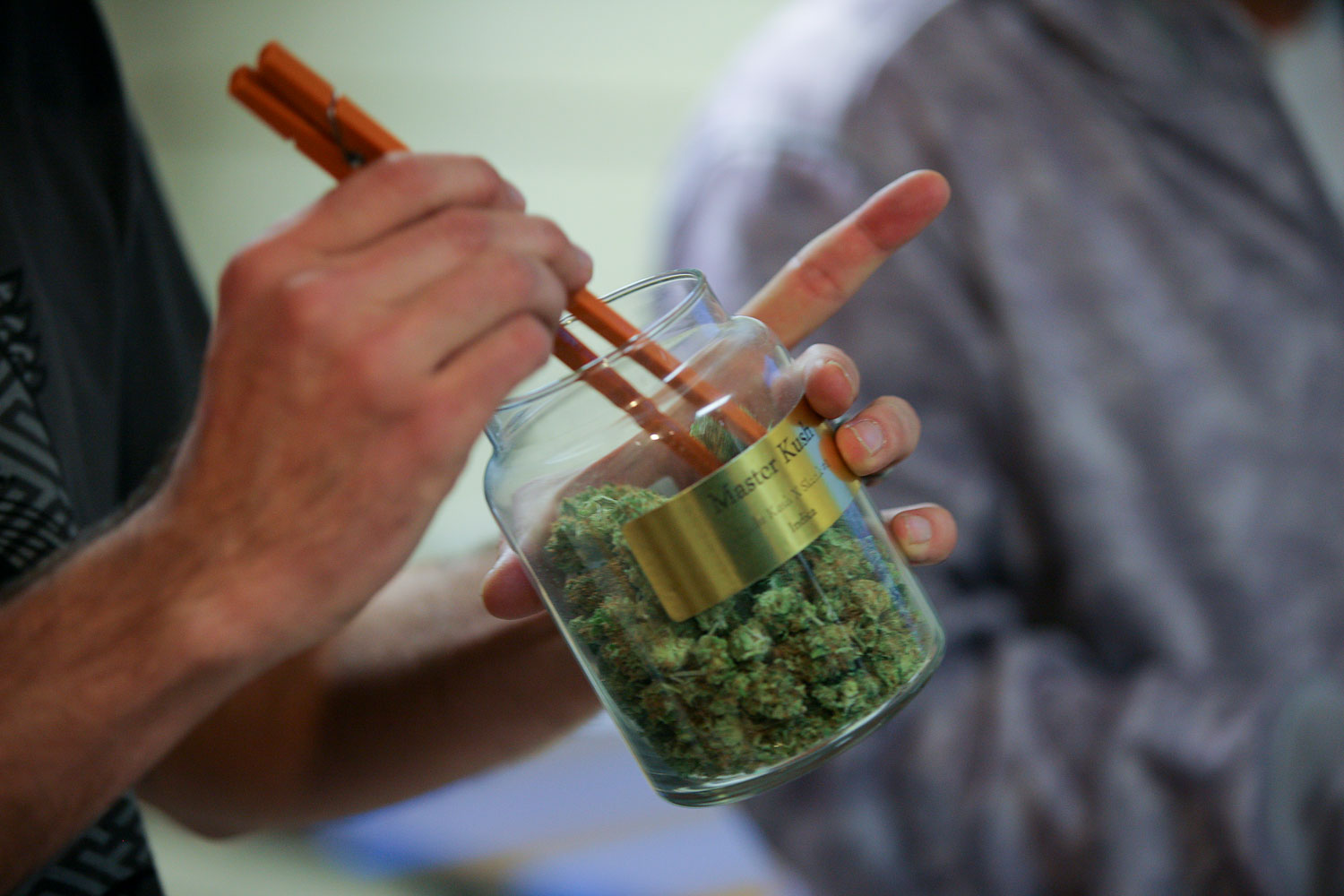 An employee pulls marijuana out of a large canister for a customer at the LoDo Wellness Center in downtown Denver, Jan. 9, 2014.
