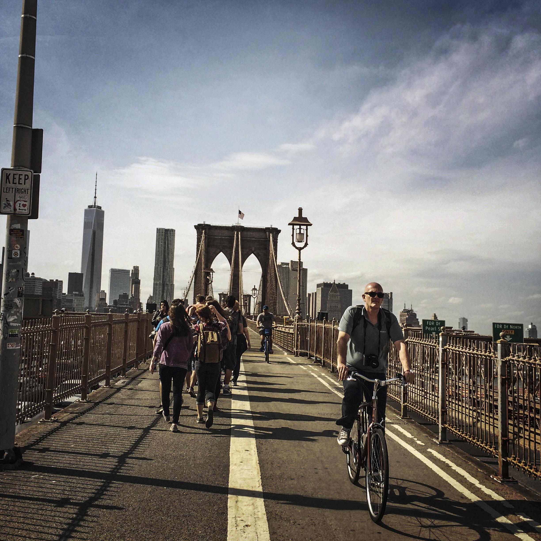People walk and ride bikes across the Brooklyn Bridge in April 2014.