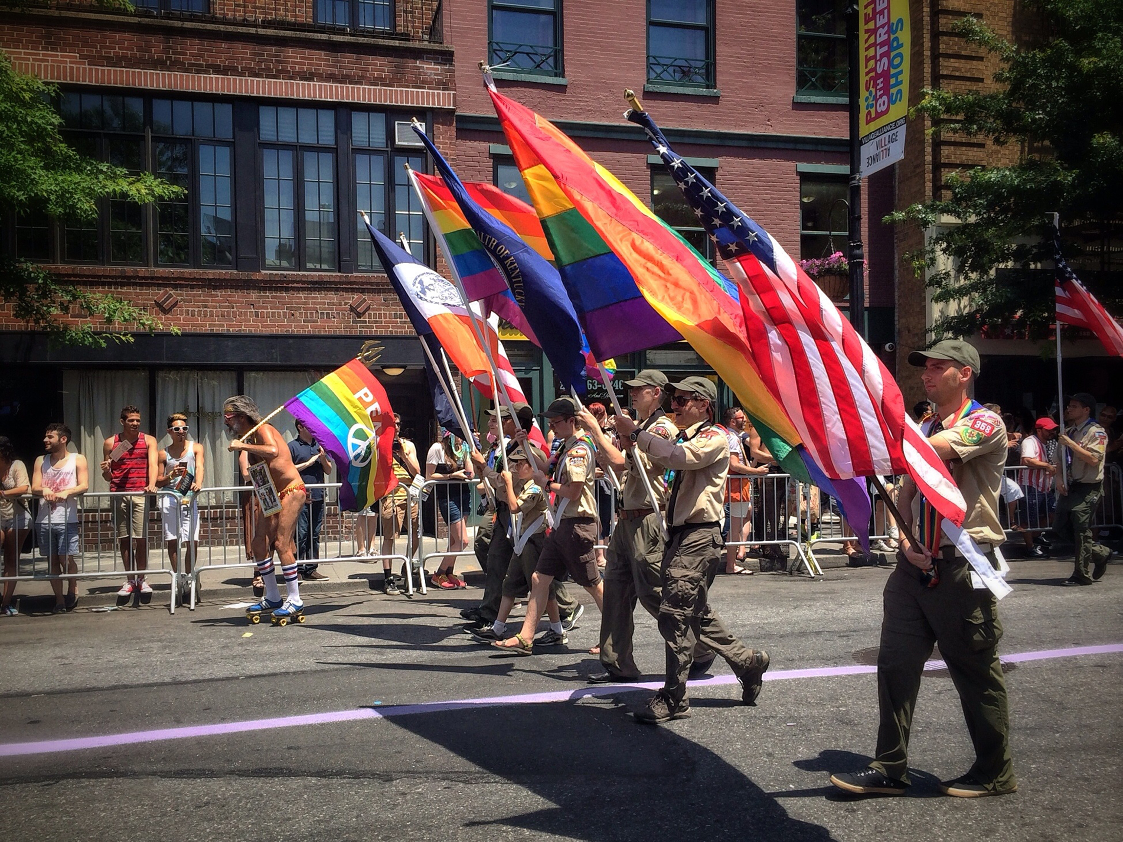 A man with a peace flag roller skates alongside the Boy Scouts of America flag bearers in the New York City Pride Parade.