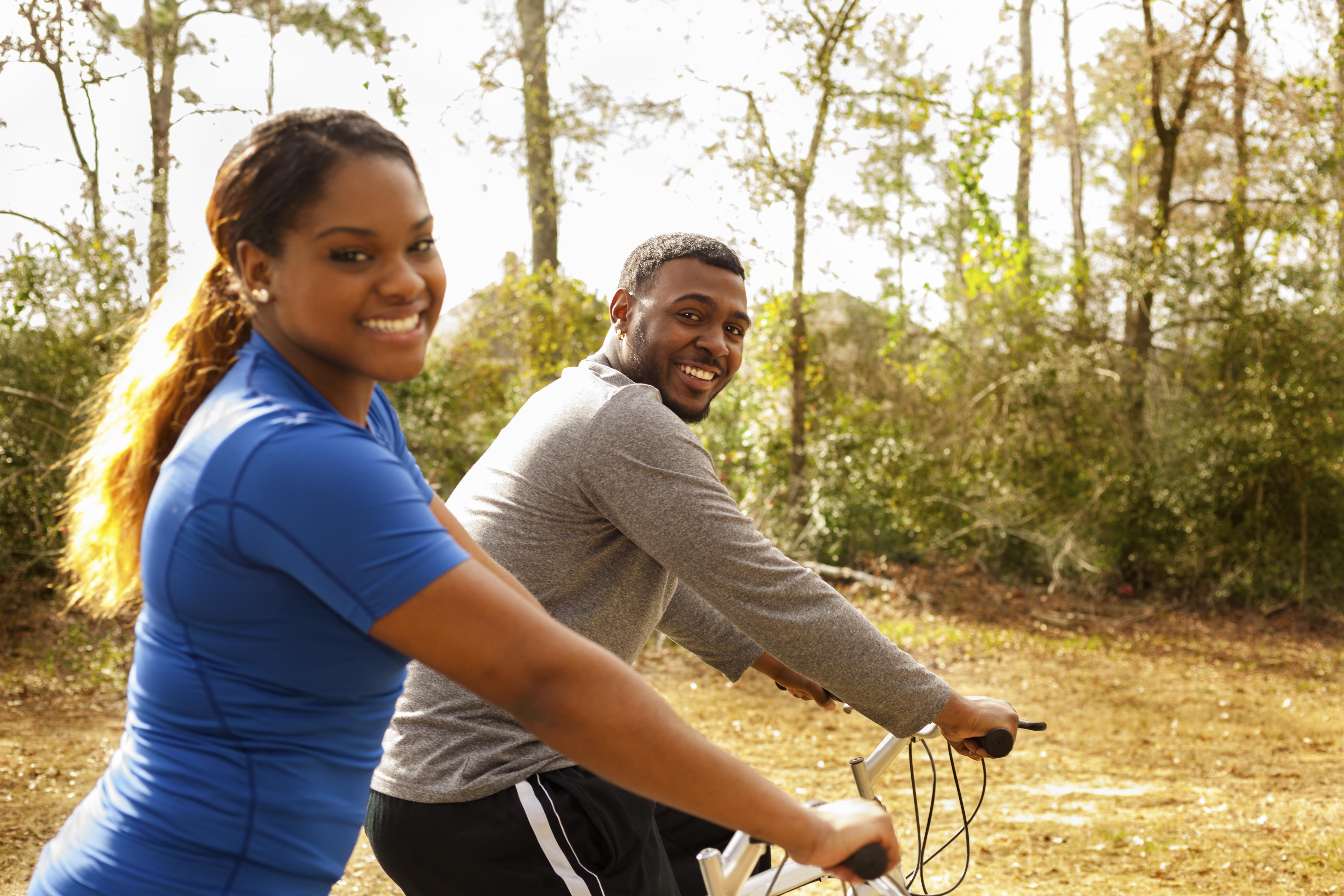 Young couple ride bikes in neighborhood.