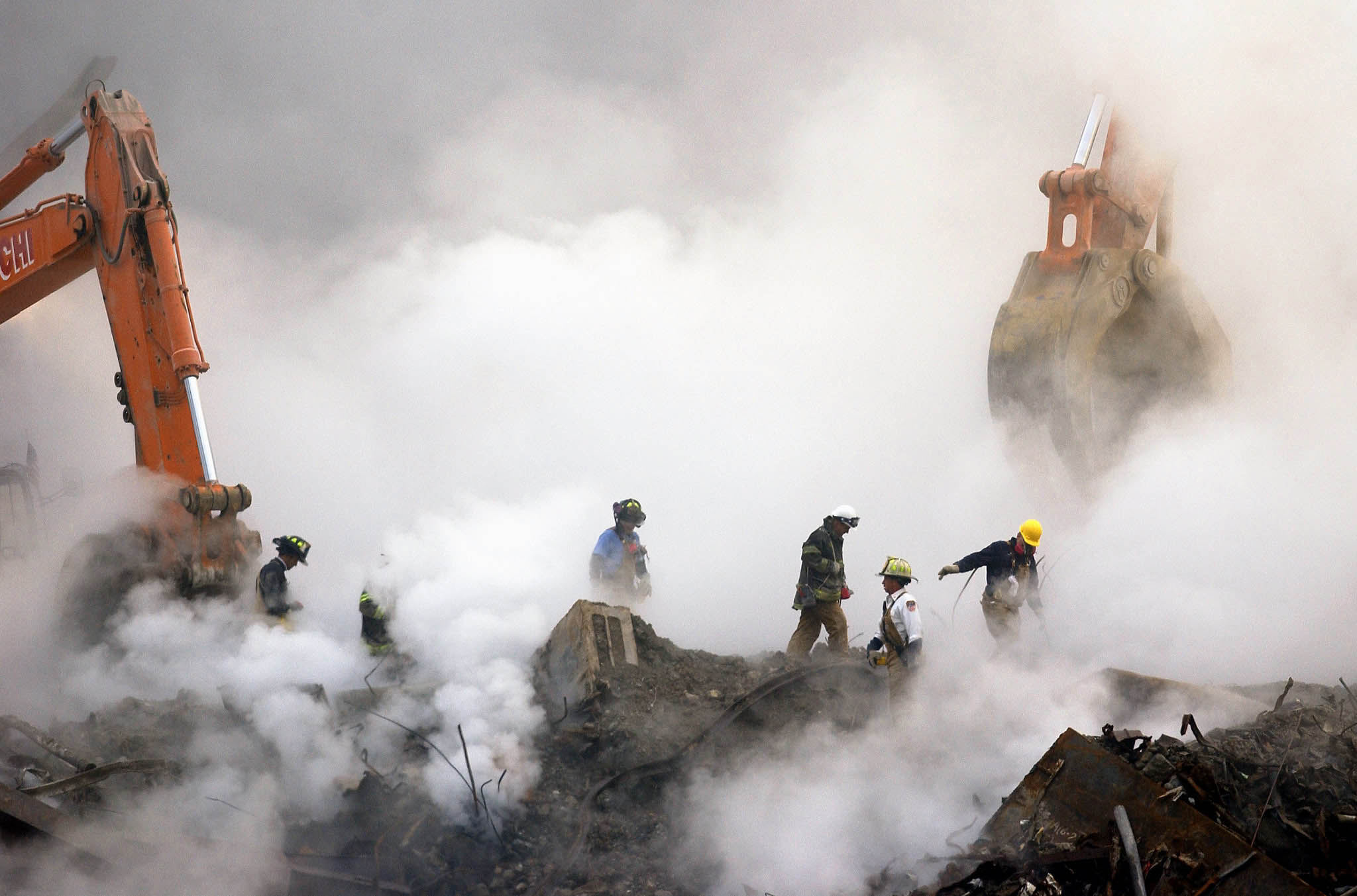 Firefighters make their way over the ruins of the World Trade Center through clouds of dust and smoke at ground zero in New York on Oct. 11, 2001.