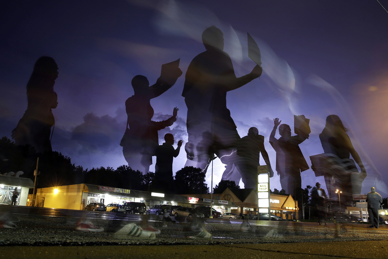 Aug. 20, 2014. In this photo taken with a long exposure, protesters march in the street as lightning flashes in the distance in Ferguson, Mo.