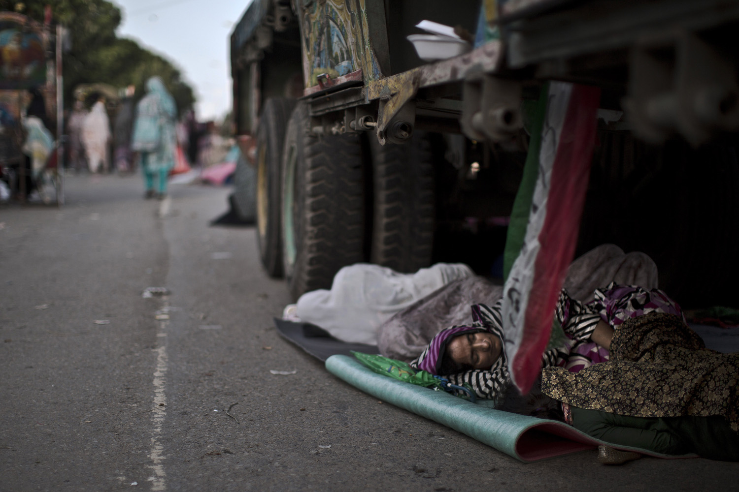 Aug. 17, 2014. A supporter of anti-government cleric Tahir-ul-Qadri, sleeps on the ground under a truck, during a protest, in Islamabad, Pakistan, Sunday, Qadri led massive rallies Saturday in Pakistanís capital, demanding Prime Minister Nawaz Sharif step down over alleged fraud in last yearís election in front of thousands of protesters.