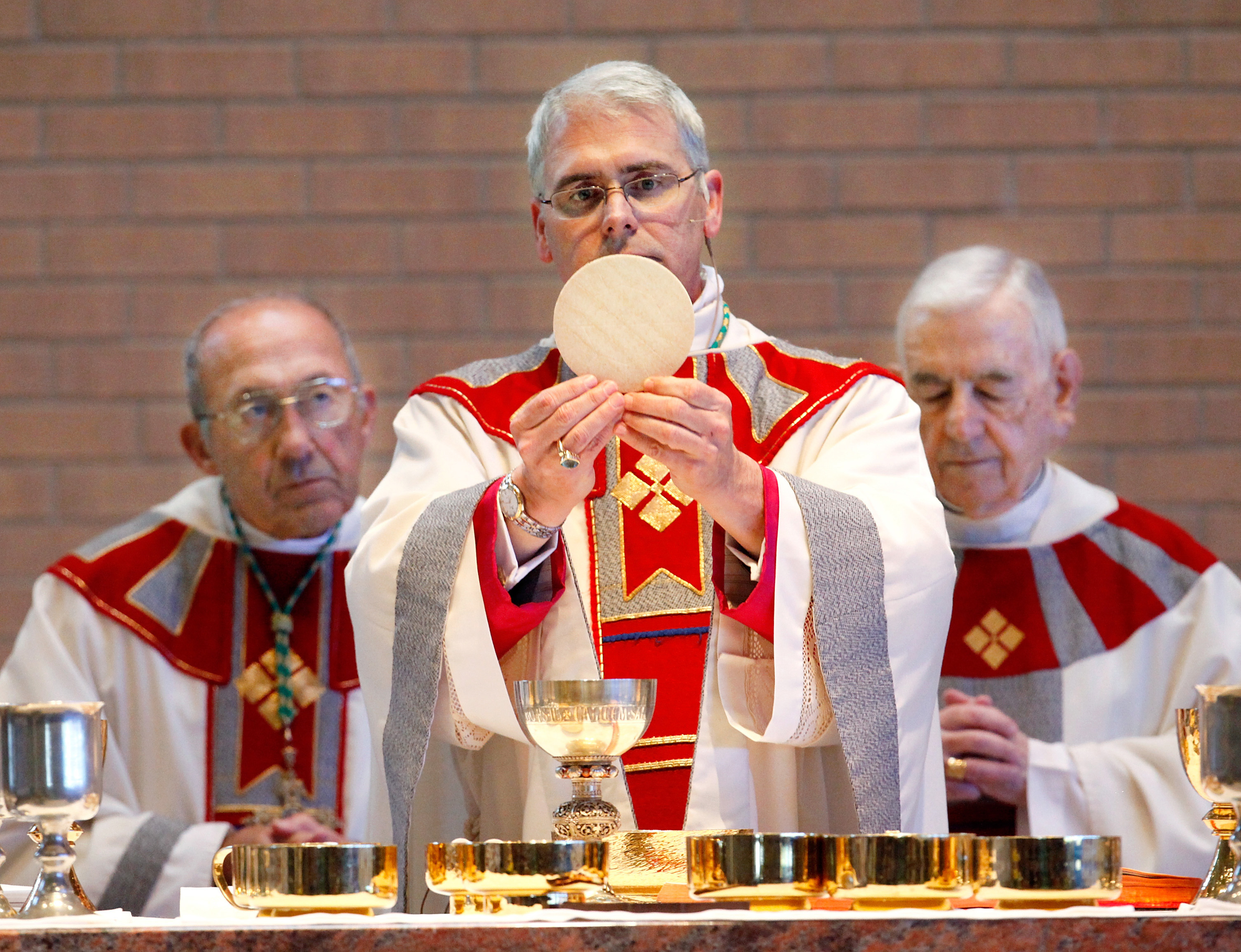 In this Feb. 11, 2011 file photo, Archbishop Paul Coakley, center, holds a communion wafer as he is installed as the fourth archbishop of the Oklahoma City Archdiocese in a ceremony at St. John the Baptist Catholic Church, in Edmond, Okla.