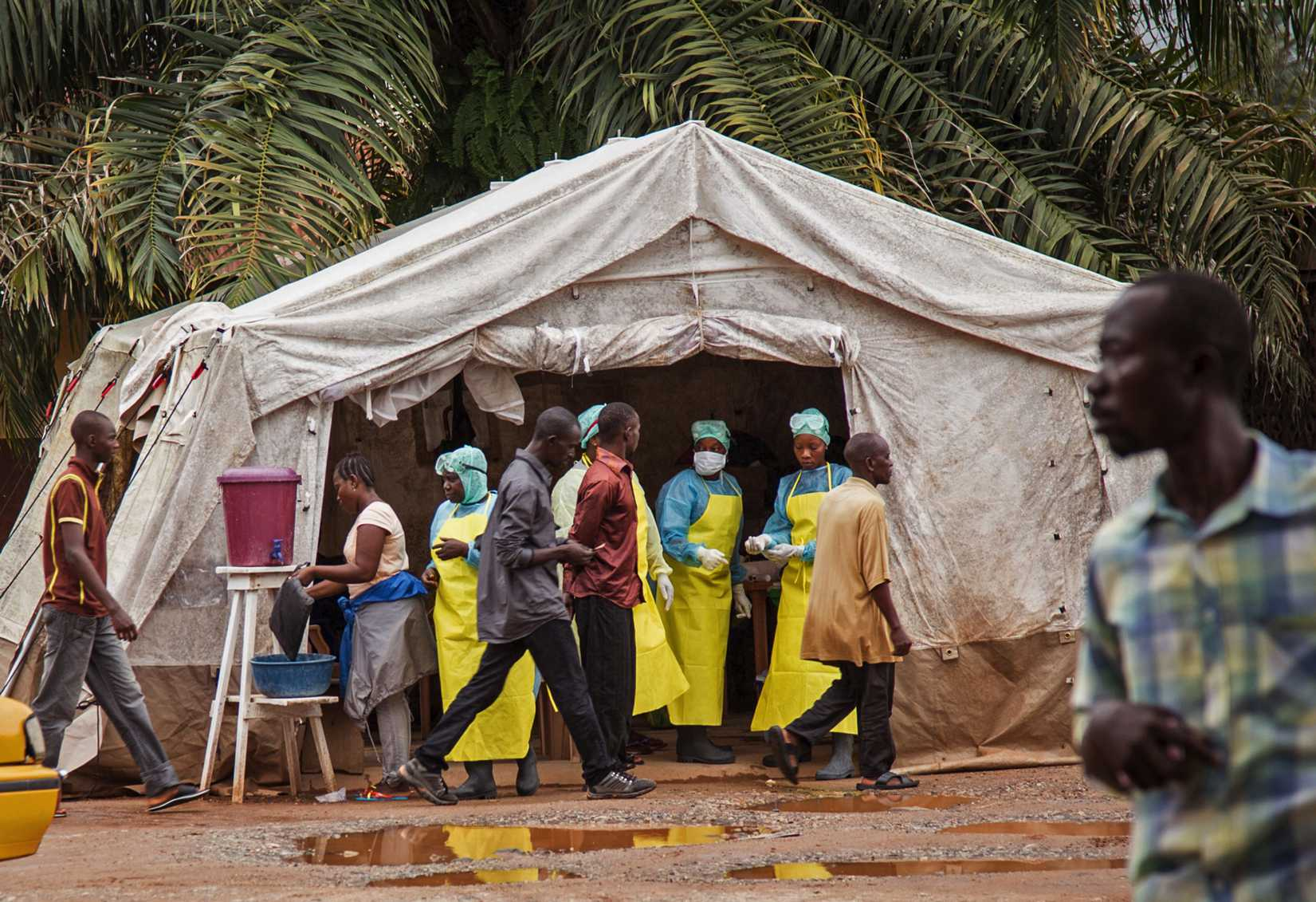 Health workers screen people for the deadly Ebola virus before entering the Kenema Government Hospital in Kenema, 300 kilometers, (186 miles) from the capital city of Freetown, Sierra Leone on August 9, 2014.