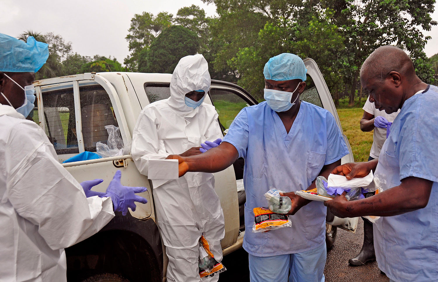 Health workers are handed personal protective gear by a team leader, right, before collecting the bodies of the deceased from streets in Monrovia, Liberia, Aug. 16, 2014.