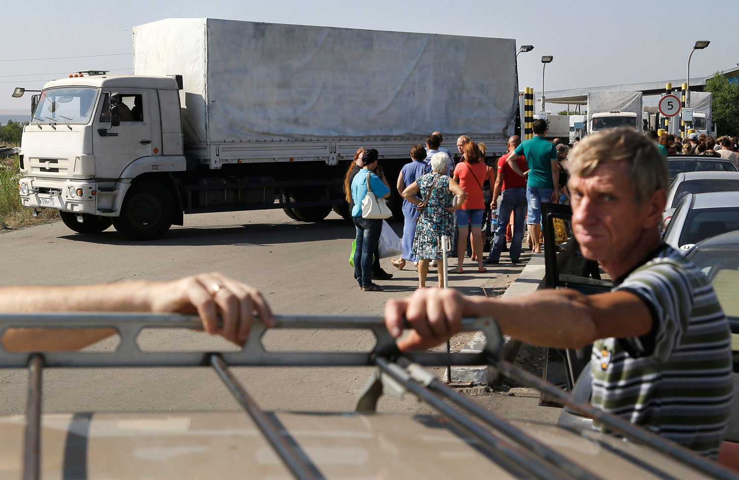 Trucks marked as being from a disputed Russian aid convoy to Ukraine return to Russia as people wait to enter Ukraine on the border post at Izvaryne, eastern Ukraine, Aug. 23, 2014.