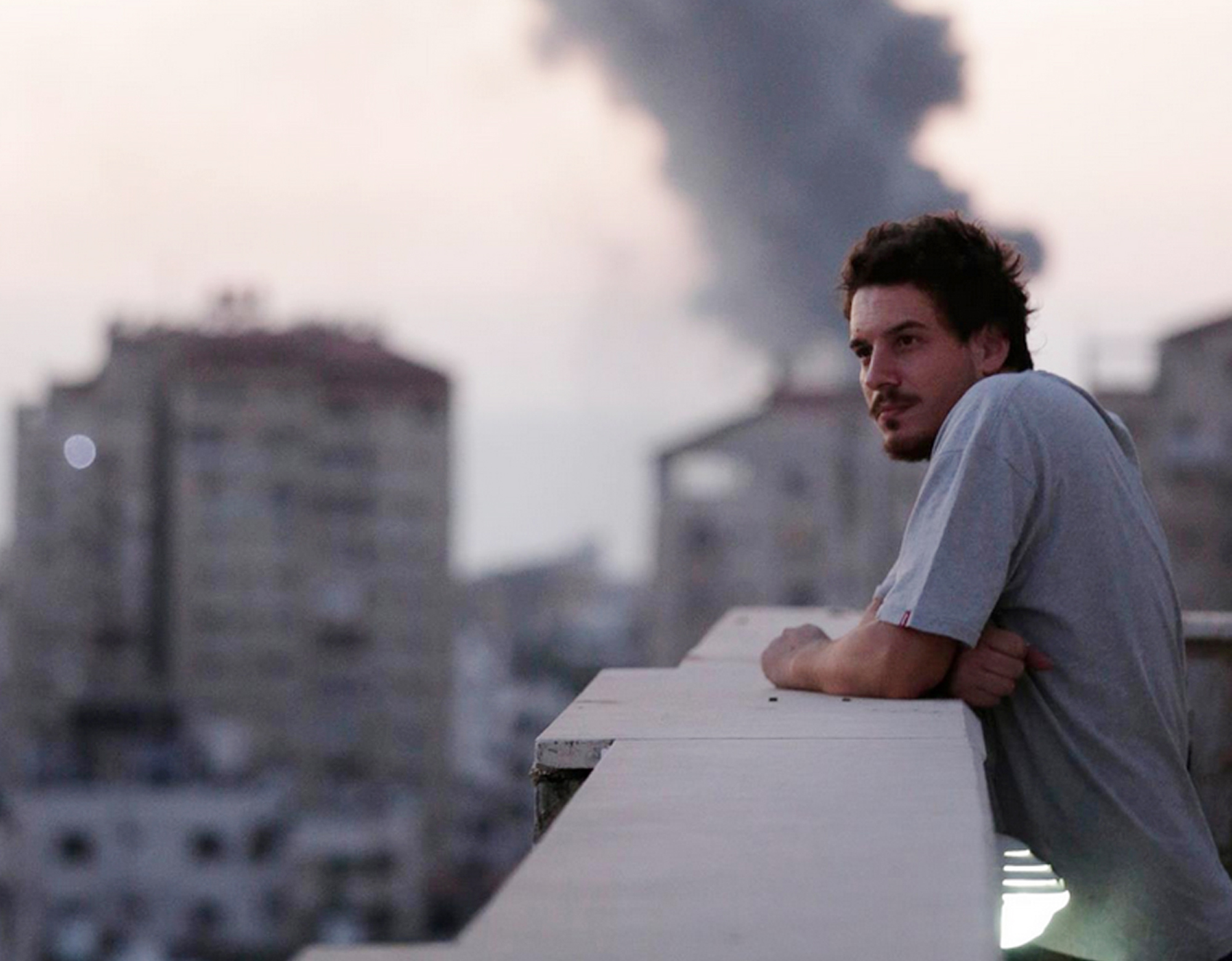 Associated Press video journalist Simone Camilli on a balcony overlooking smoke from Israeli Strikes in Gaza City. Camilli, 35, was killed in an ordnance explosion in the Gaza Strip, on Aug. 13, 2014 together with Palestinian translator Ali Shehda Abu Afash and three members of the Gaza police.