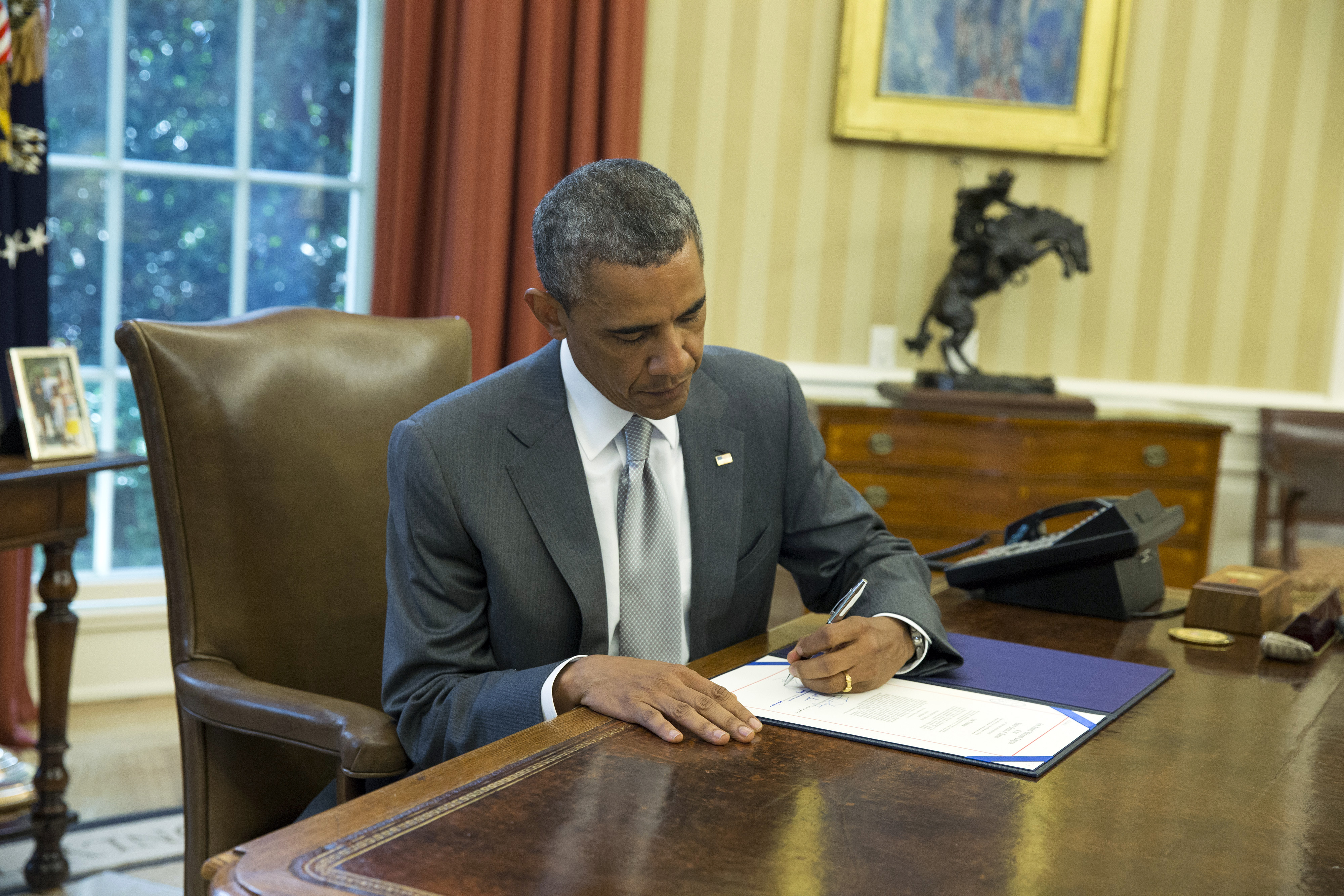 President Barack Obama signs  H.J. Res. 76,  a bill that provides an additional $225 million in U.S. taxpayer dollars for Israel's Iron Dome missile defense system, in the Oval Office of the White House, Monday, Aug. 4, 2014, in Washington.