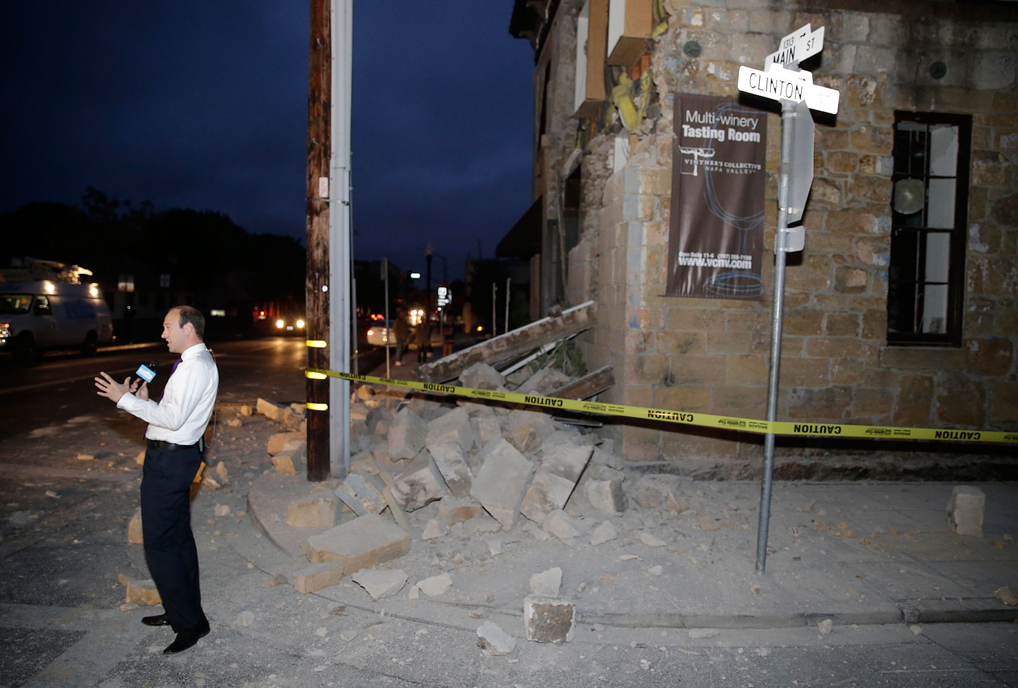 A reporter in front of the damaged Vintners Collective multi-winery tasting room in Napa, Calif.