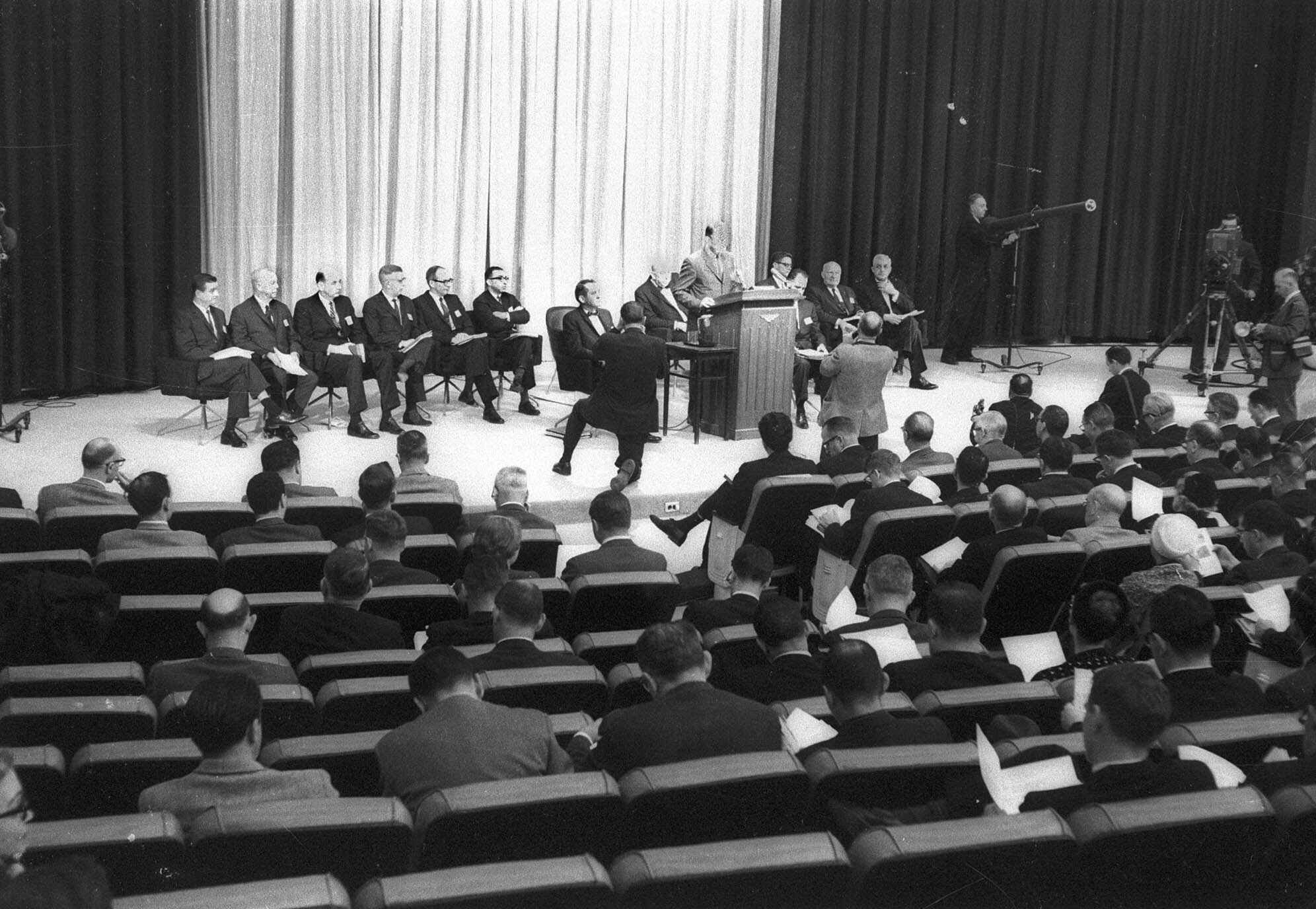 U.S. Surgeon General Luther Terry, at rostrum, answers questions on a landmark report on the dangers of smoking during a Jan. 11, 1964 news conference in Washington.  Members of his advisory committee sit behind him, with Dr. Emmanuel Farber sixth from left, with arms folded