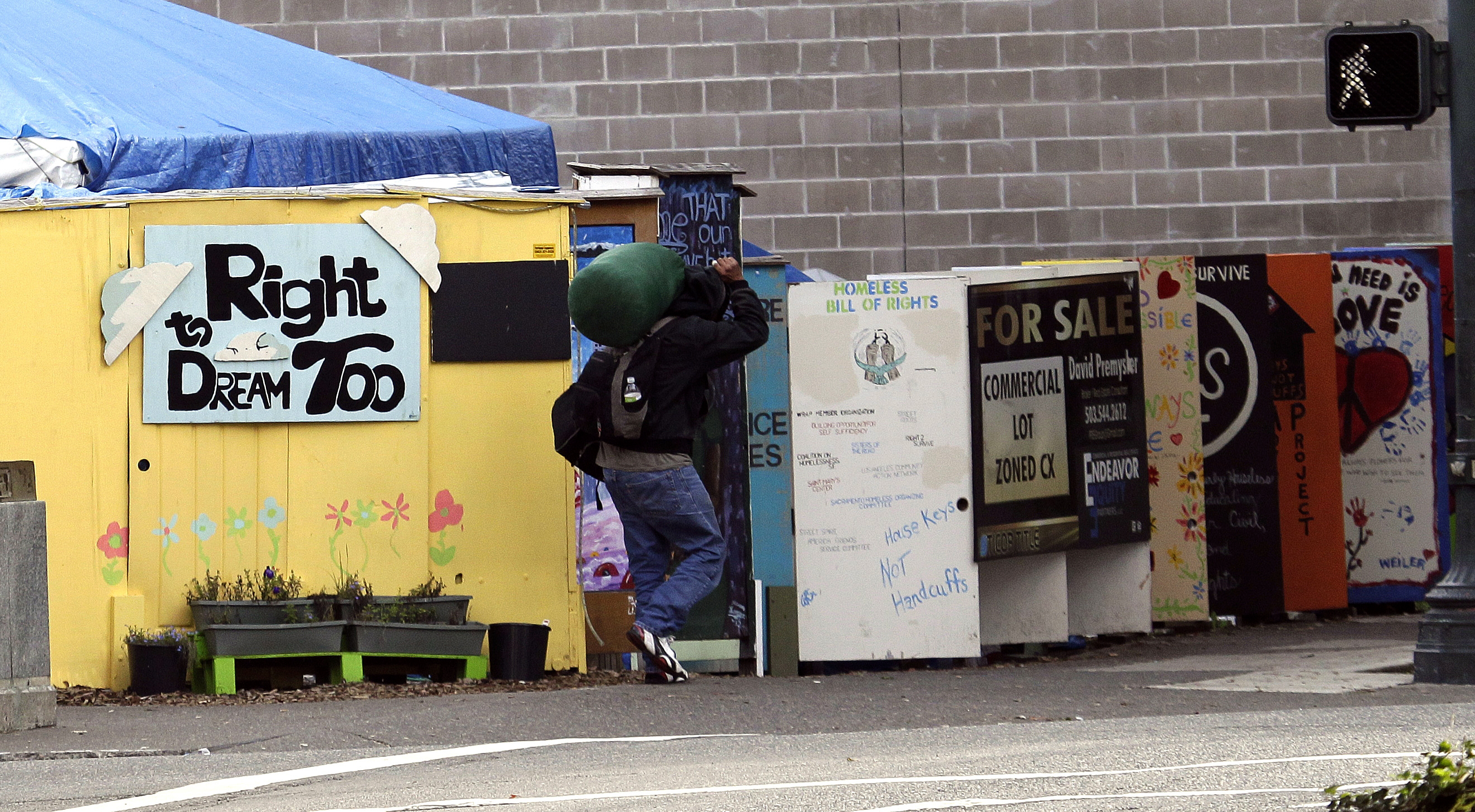 A person walks by the Right 2 Dream Too homeless camp in Portland, Ore. on Oct. 4, 2013.