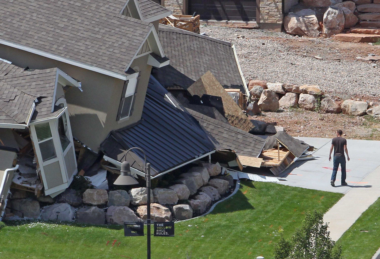 Aug. 5, 2014. A man looks at a home destroyed by a landslide in a hillside community of North Salt Lake, Utah.