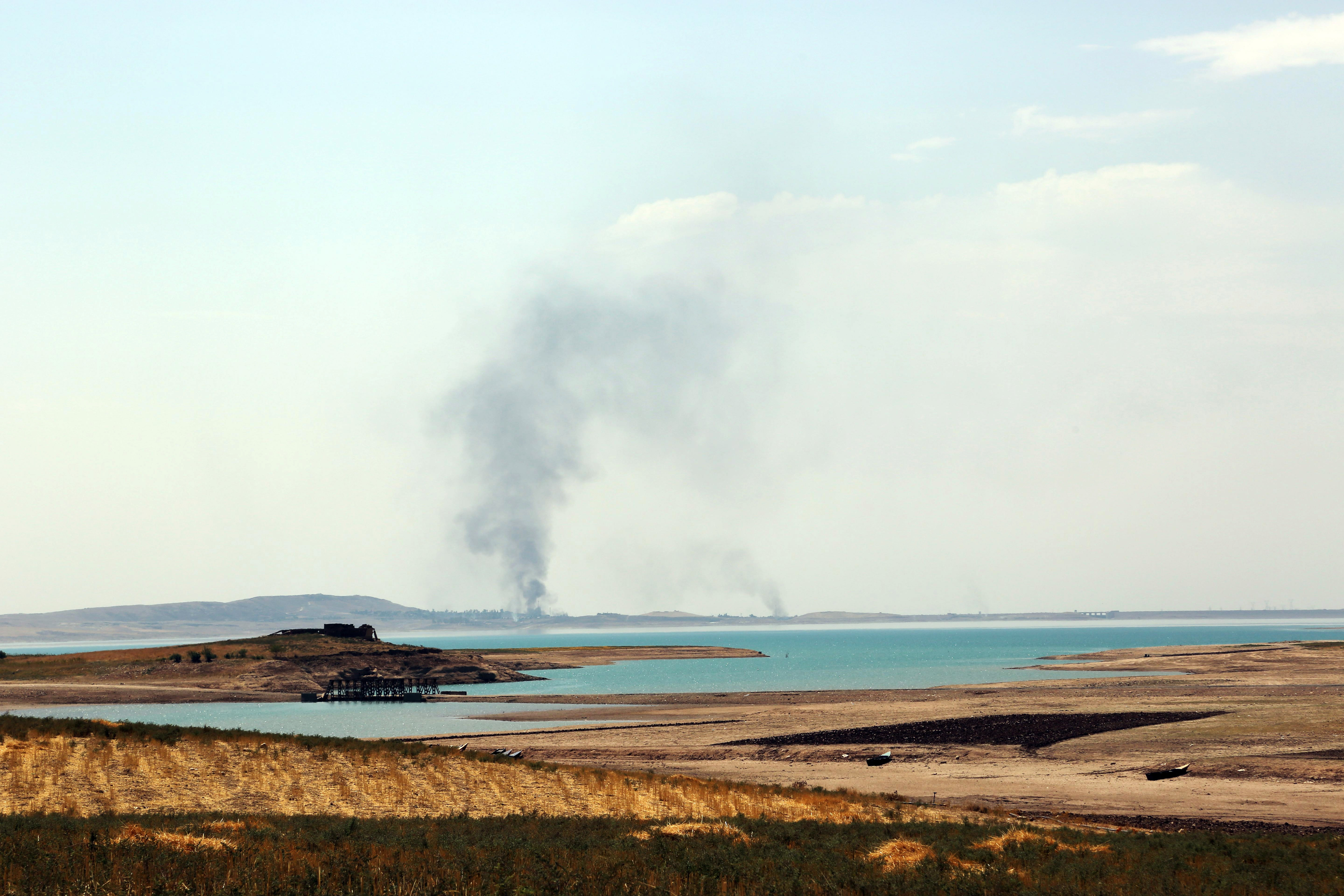 Smoke rises during airstrikes targeting Islamic State militants at the Mosul Dam outside Mosul, Iraq, Monday, Aug. 18, 2014.