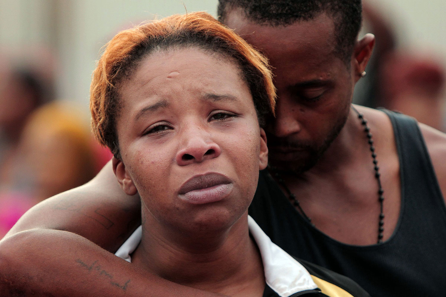 Lesley McSpadden, left, is comforted by her husband, Louis Head, after her 18-year-old son, Michael Brown was shot and killed by police in the middle of the street in Ferguson, Mo., near St. Louis on Aug. 9, 2014.