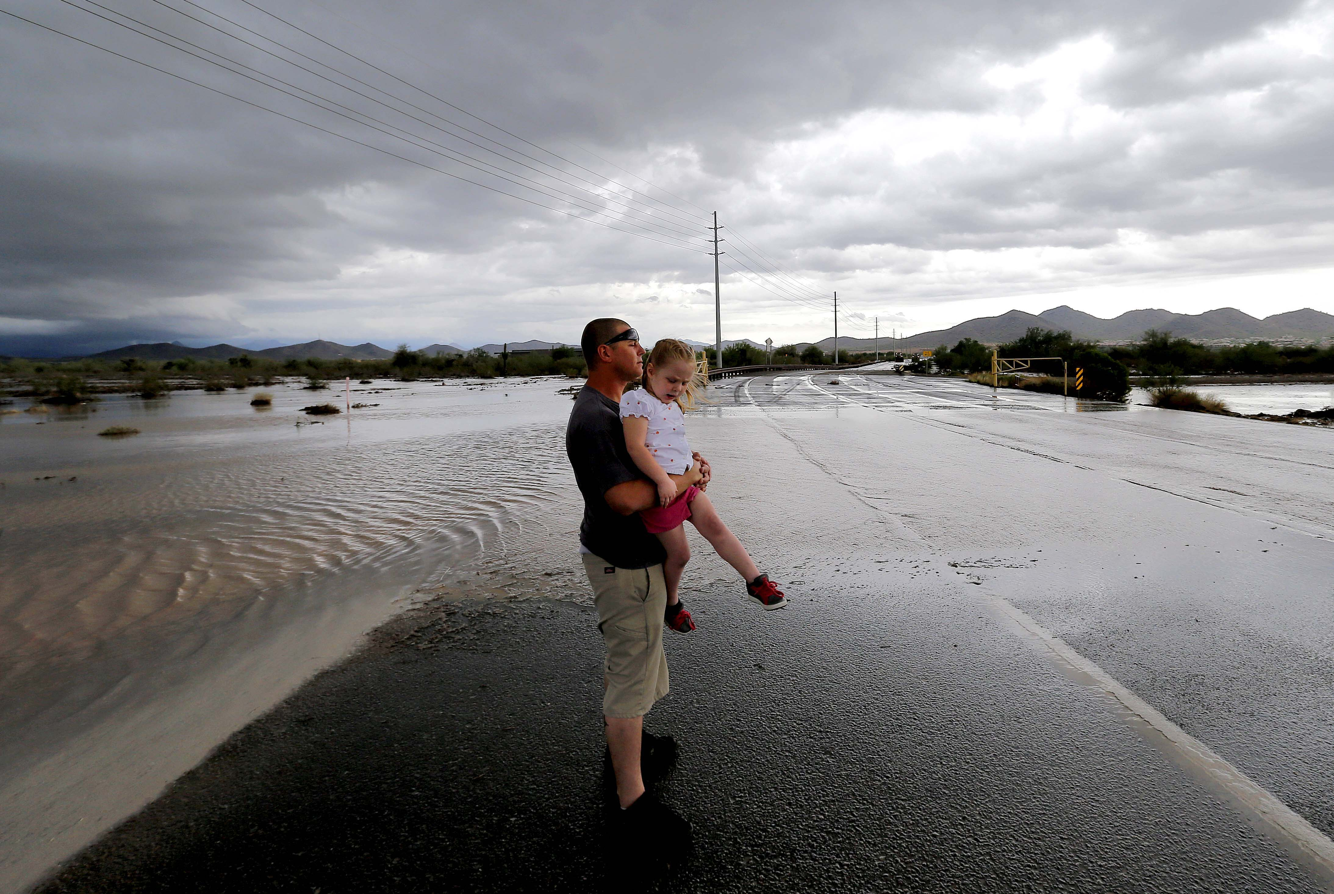 Josh Groves, and his daughter Abagayle Groves, 3, wait to cross the road as waters overrun Skunk Creek through the Sonoran Desert, Aug. 19, 2014, in northwestern Phoenix.
