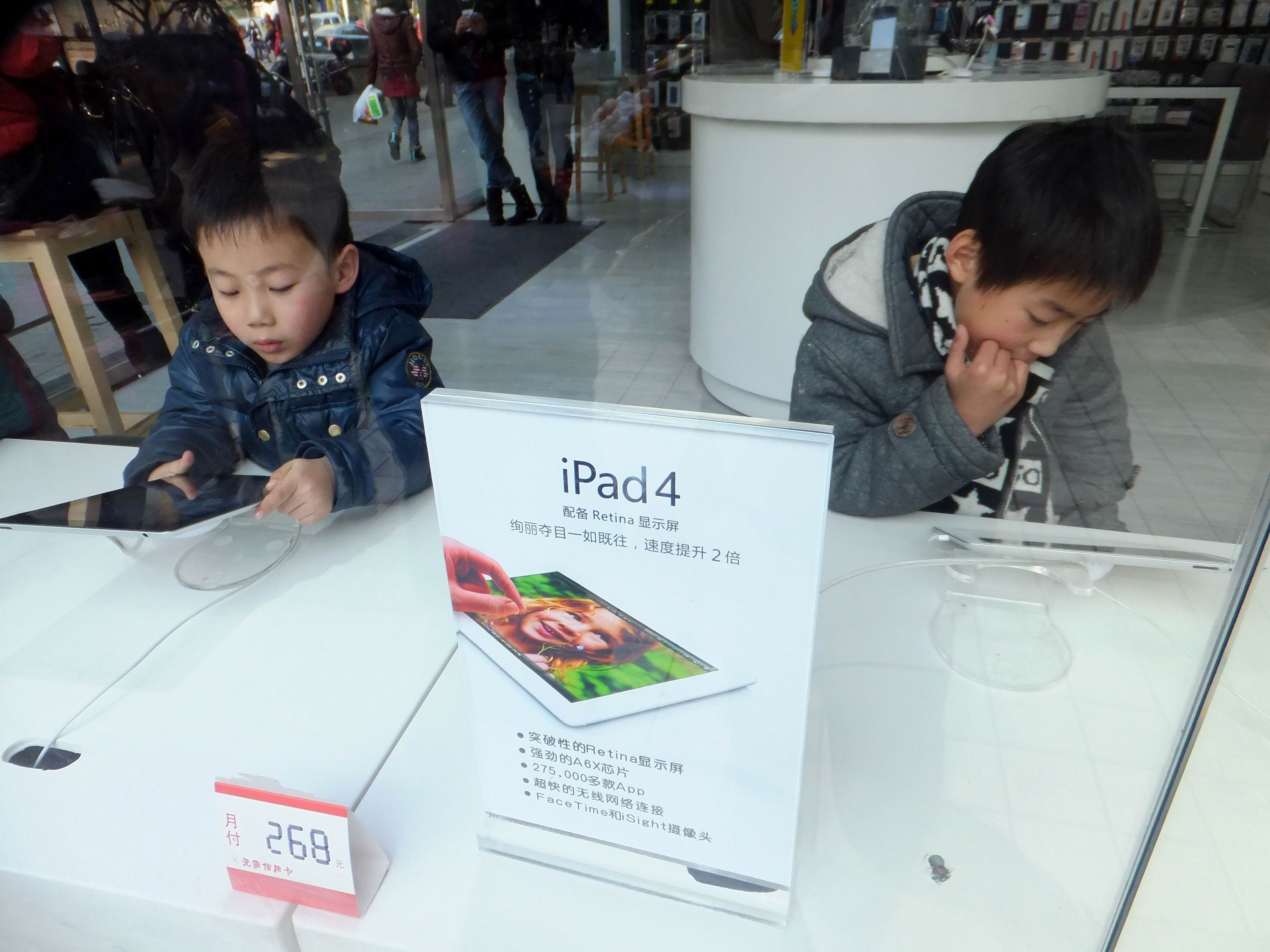 Young Chinese customers try out iPad 4 tablet computers at a branch of China Mobile in Chongqing, China, 31 December 2012.