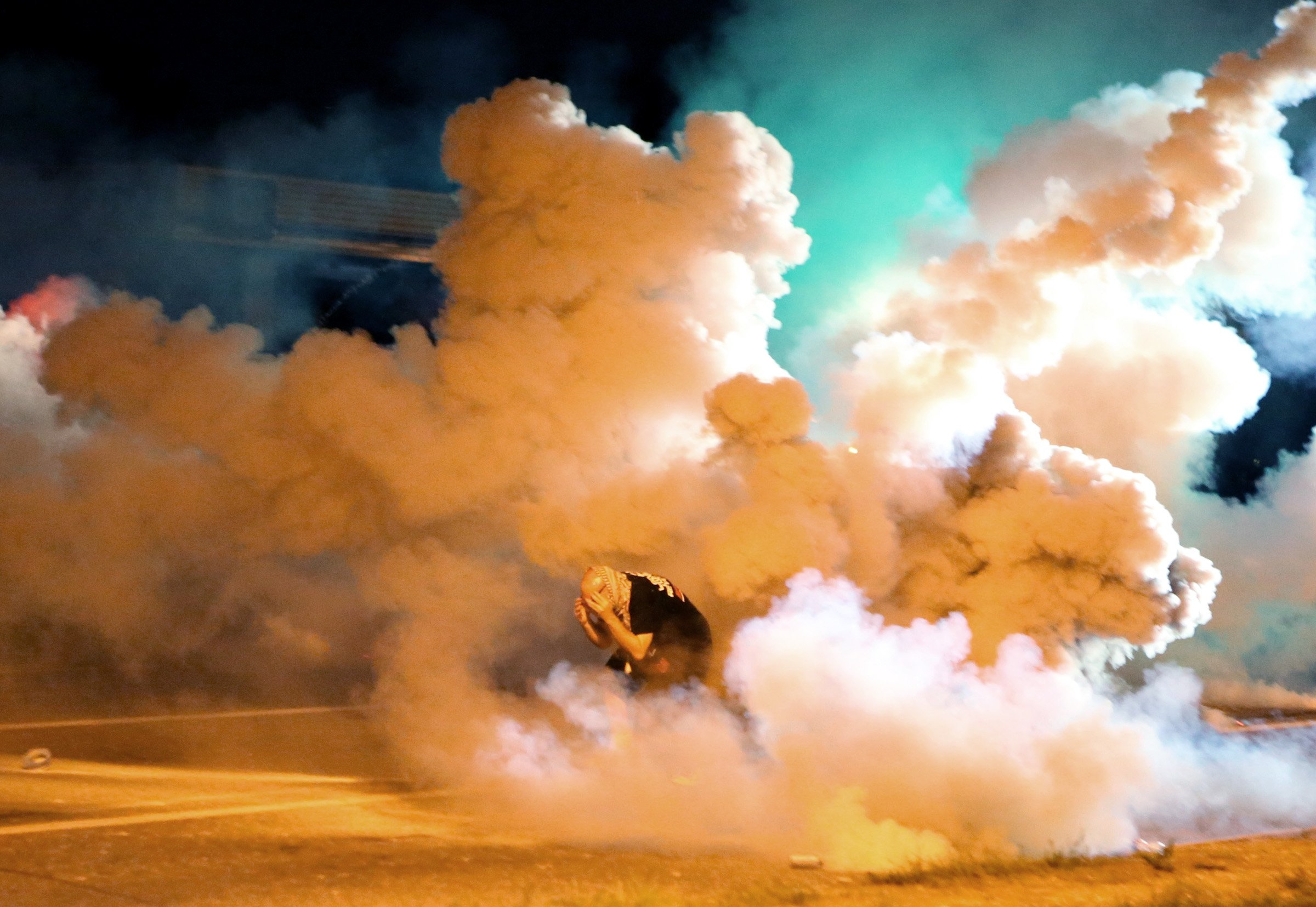 A protester takes shelter from smoke billowing around him in Ferguson, Mo. on Aug. 13, 2014.