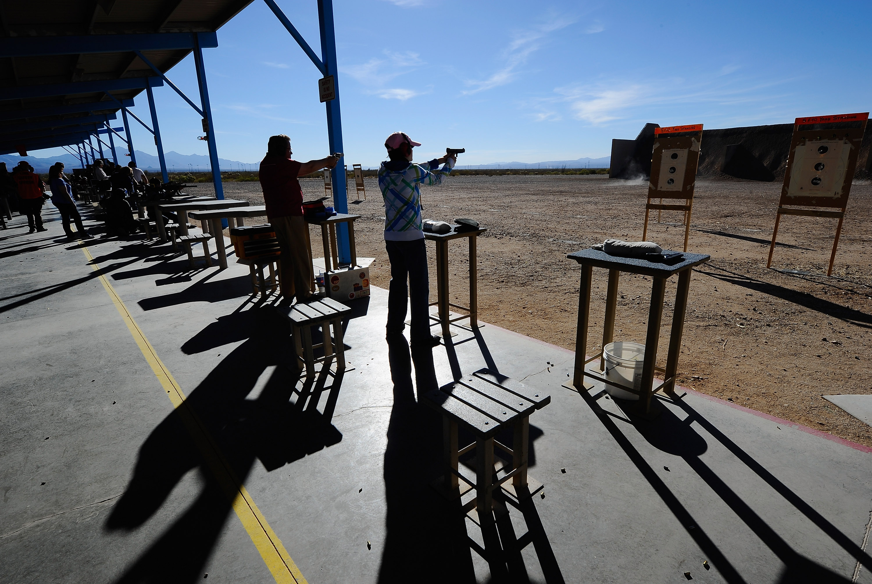 People shoot their guns at the Southwest Regional Park shooting range near the Crossroads of the West Gun Show at the Pima County Fairgrounds in Tucson, Ariz.