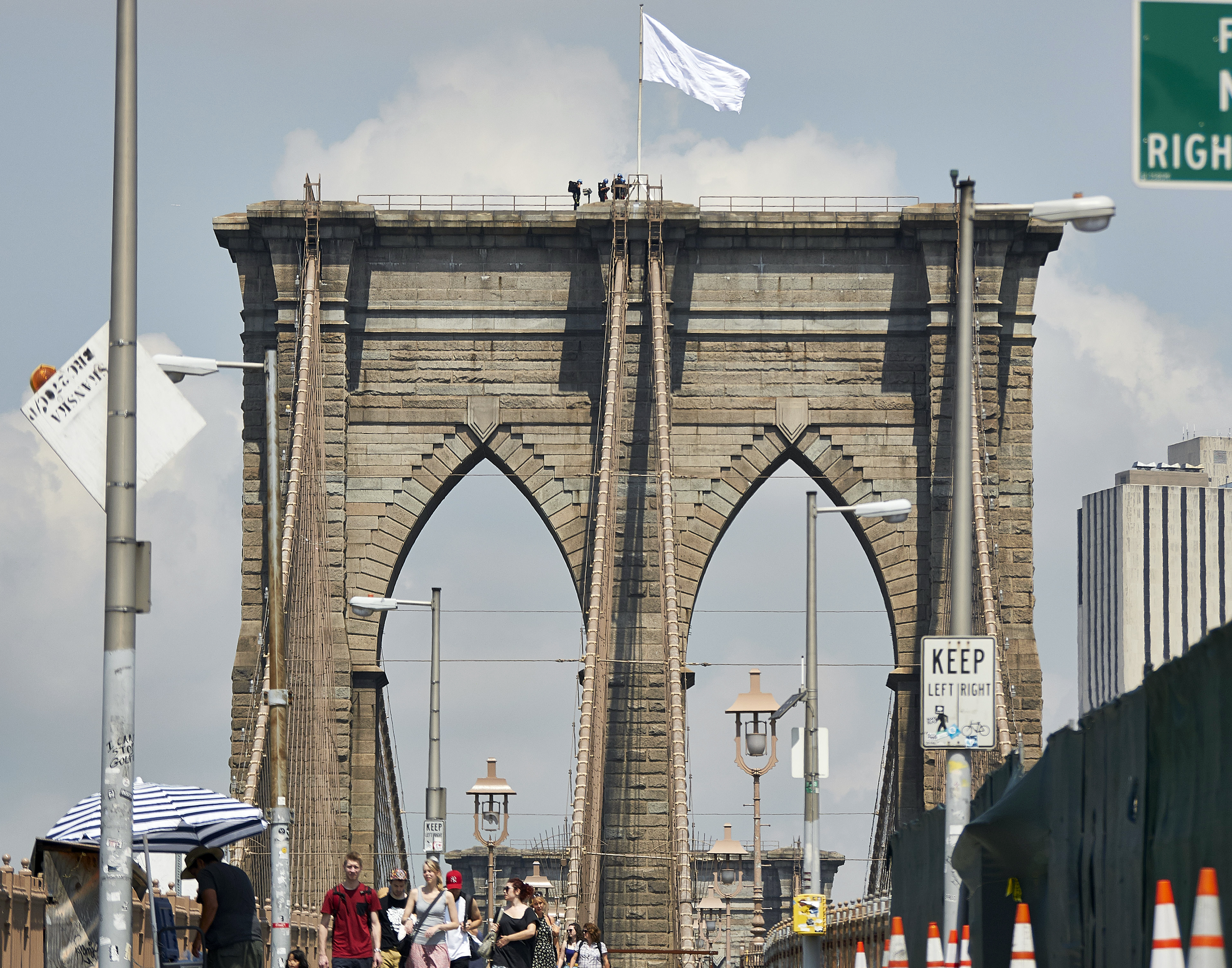 Members of the New York Police Department scale the Brooklyn Bridge after two high-flying American flags were swiped from atop the Brooklyn Bridge overnight and replaced with two white flags