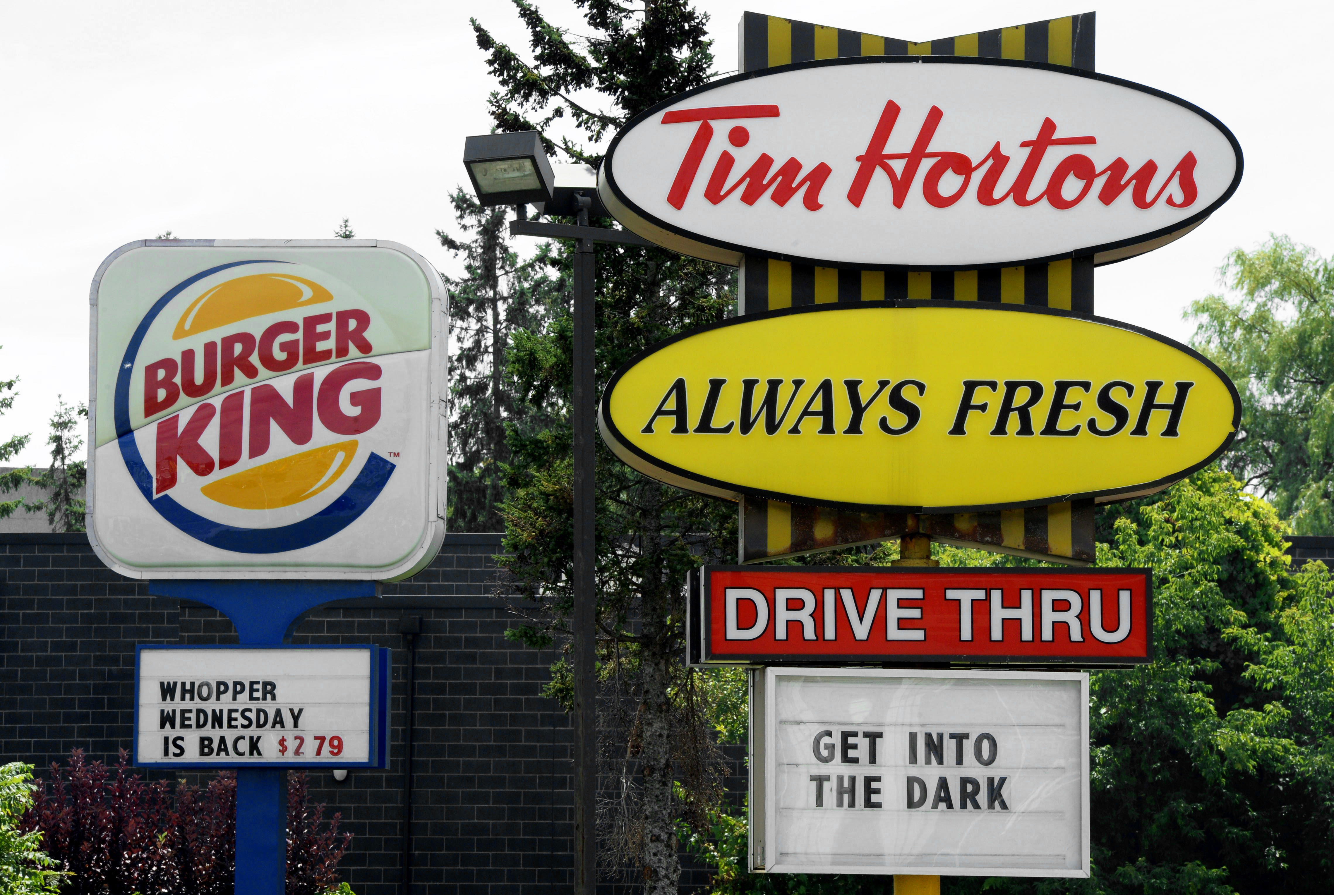 A Burger King sign and a Tim Hortons sign are displayed on St. Laurent Boulevard in Ottawa, Canada on Aug. 25, 2014.