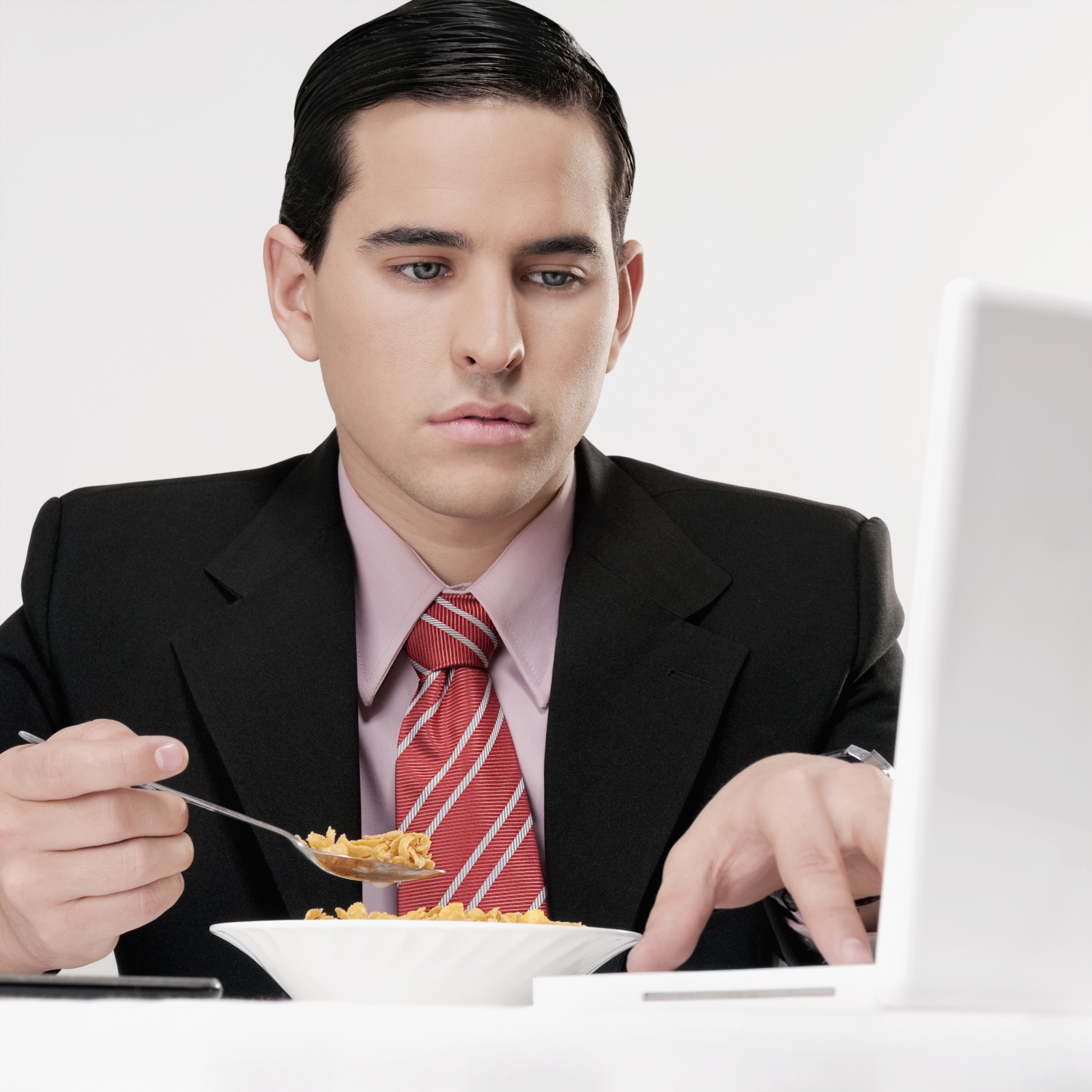 Businessman working on a laptop at breakfast table