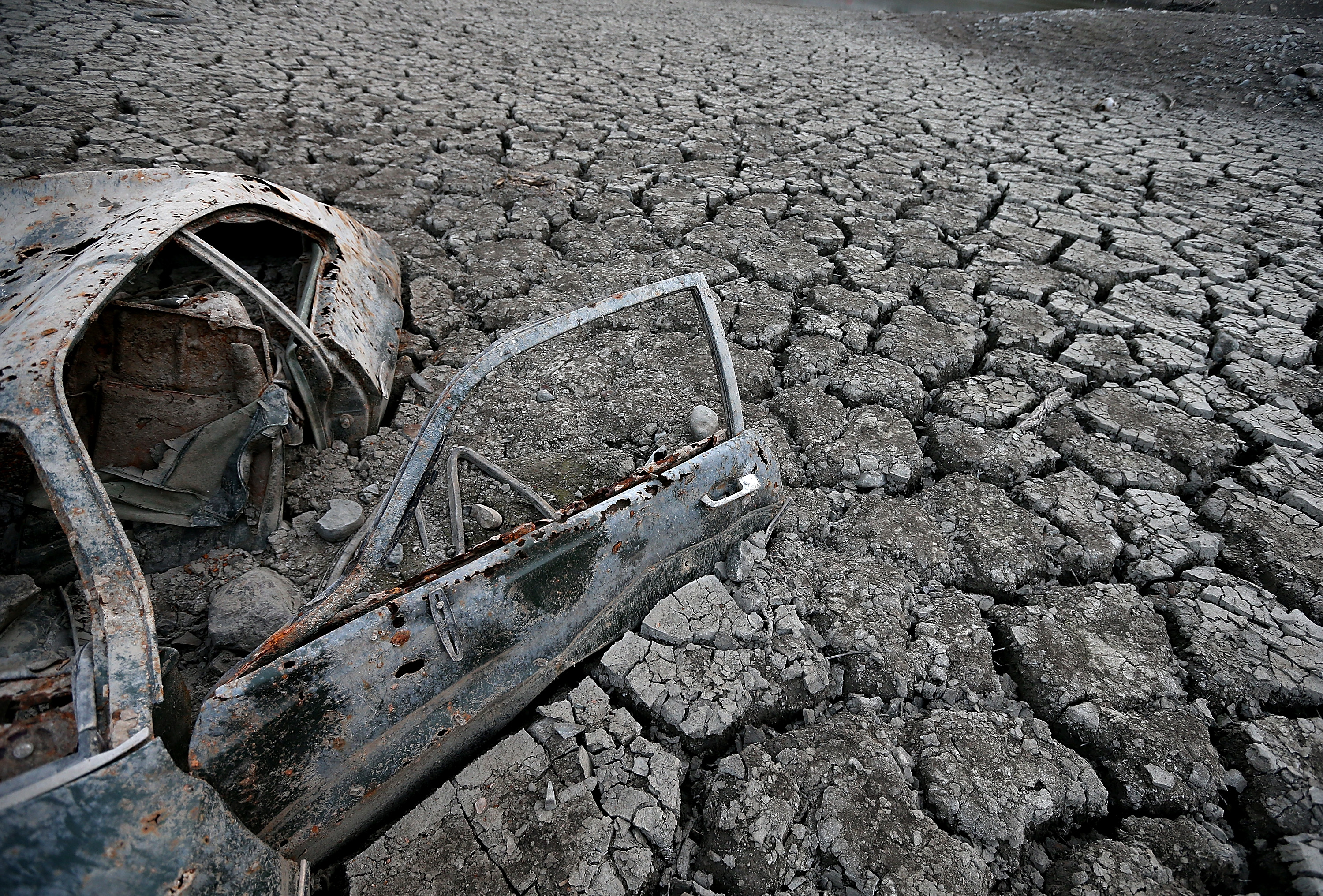 A car sits in dried and cracked earth of what was the bottom of the Almaden Reservoir on Jan. 28, 2014 in San Jose, Calif.