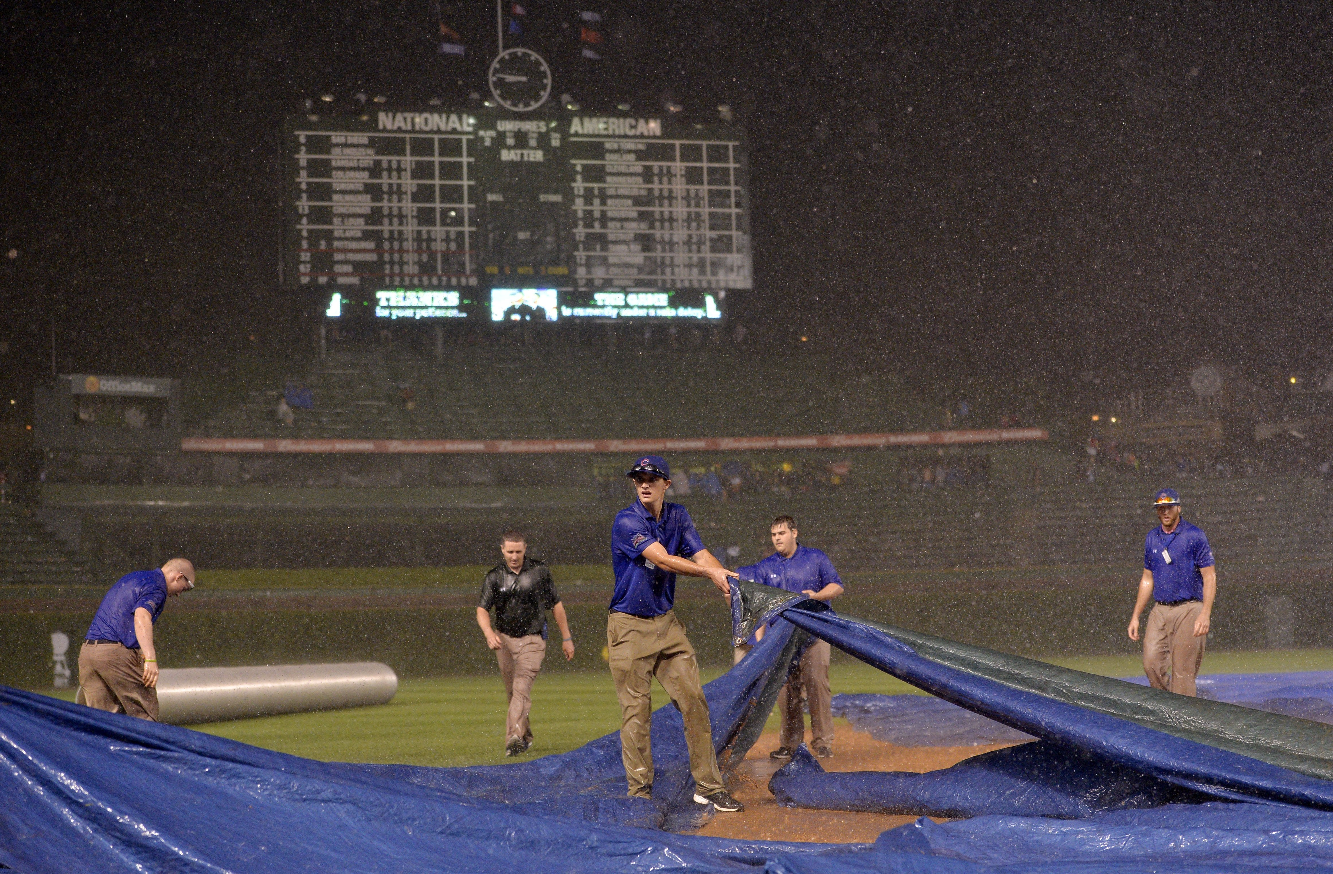 Chicago Cubs ground crew members struggle to get the tarp on the field as rain falls during the fifth inning of the Chicago Cubs game against the San Francisco Giants at Wrigley Field on August 19, 2014 in Chicago.