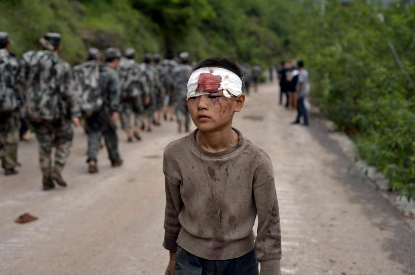 An injured child walks past rescuers heading towards the epicenter of an earthquake that struck the town of Longtoushan in Ludian county in southwest China's Yunnan province, Aug. 4, 2014