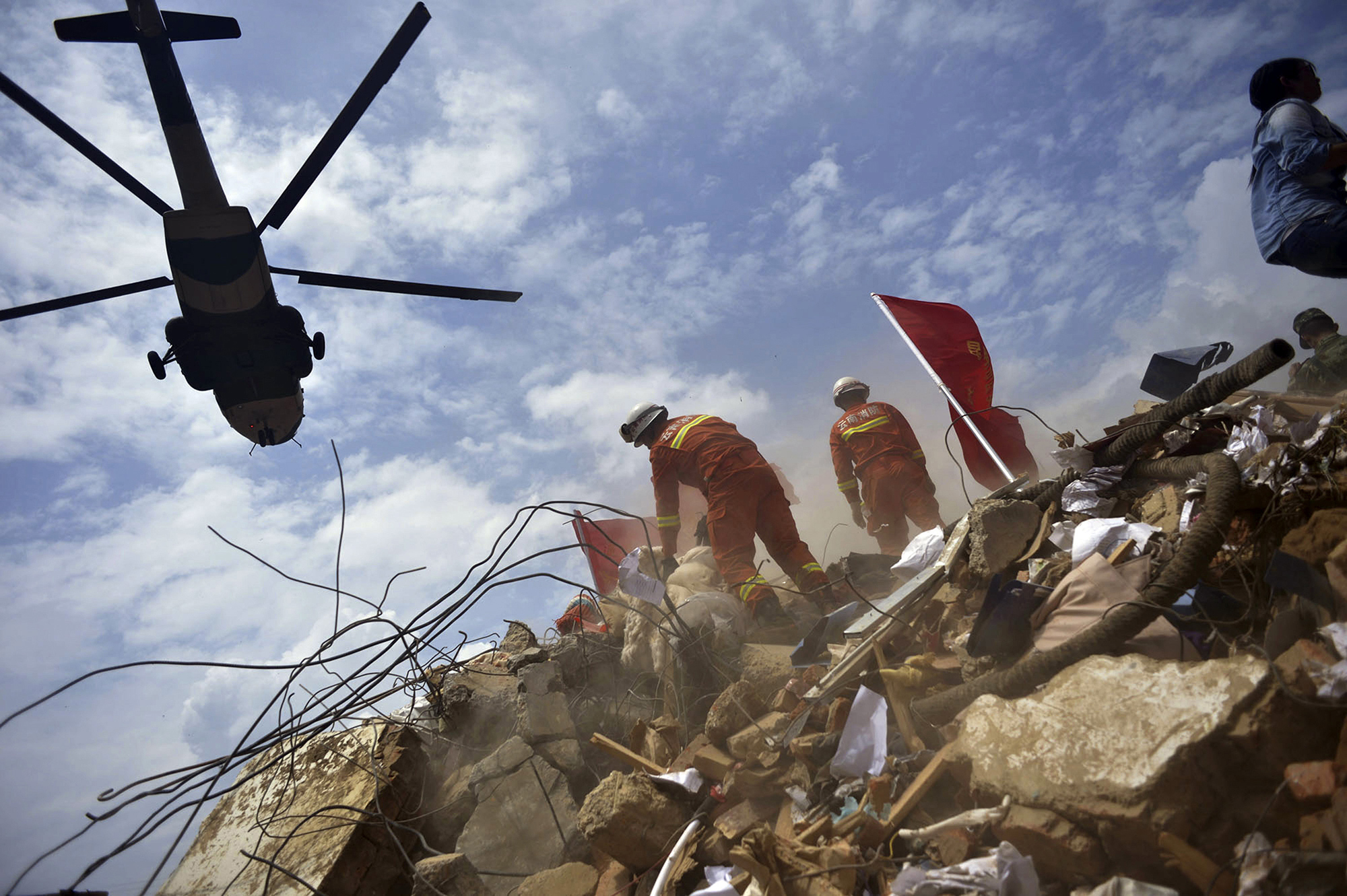 A helicopter flies over rescue workers at the epicenter of Sunday's earthquake that struck the town of Longtoushan in Ludian County in southwest China's Yunnan Province, Aug. 4, 2014.