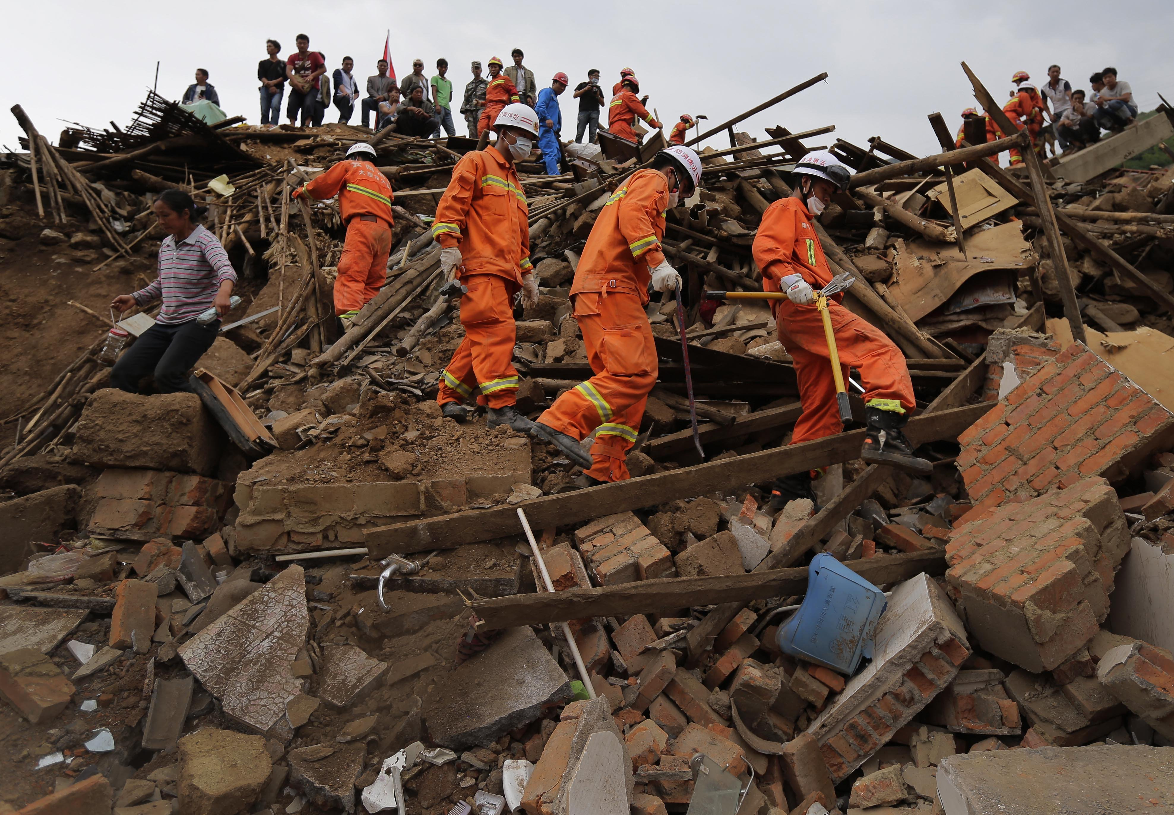 Rescuers and a villager walk past rubbles from destroyed houses following a massive earthquake in the town of Longtoushan in Ludian County in southwest China's Yunnan Province, Aug. 5, 2014.