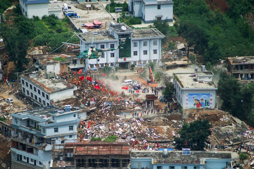 A helicopter flies above collapsed houses after a magnitude 6.3 earthquake hit Longtoushan town, Ludian county, Zhaotong, Yunnan province on Aug. 4, 2014.