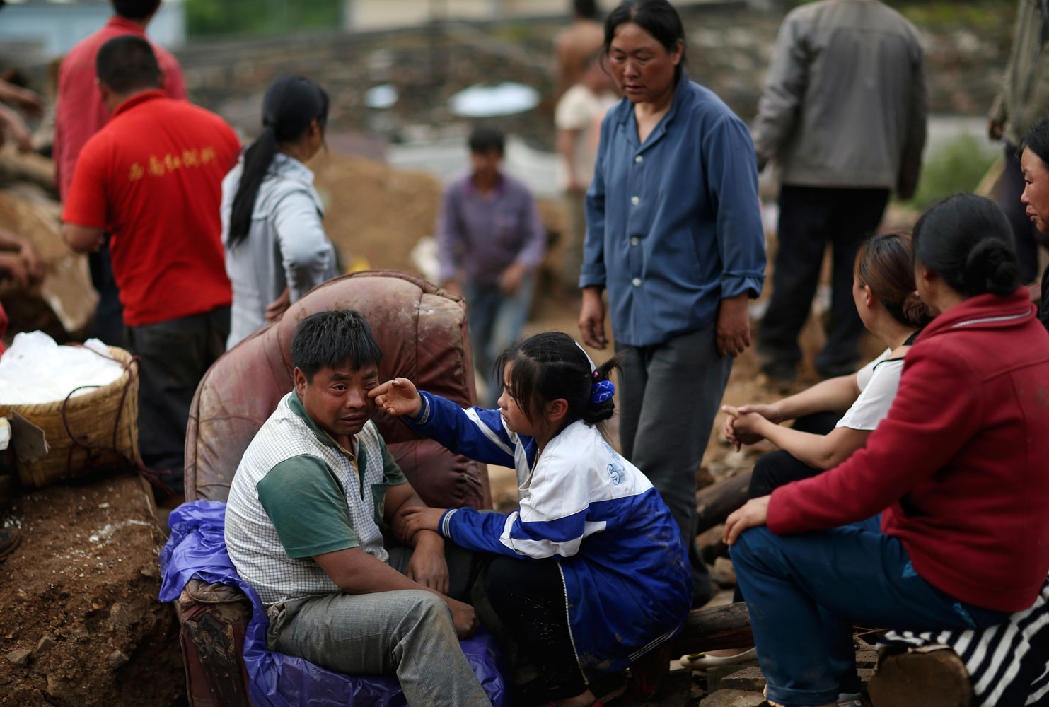 Liu Jiali (front L) cries as his daughter (C) wipes his tear after an earthquake killed Liu's wife and two other children in Longtoushan township of Ludian county, Yunnan province  on Aug. 4, 2014.