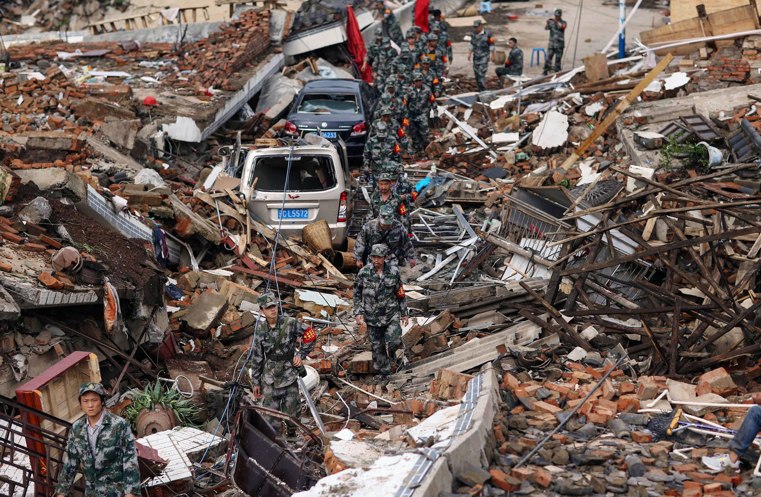Rescuers search for survivors as they walk among debris of collapsed buildings after an earthquake hit Longtoushan township of Ludian county, Yunnan provinceon Aug. 4, 2014.